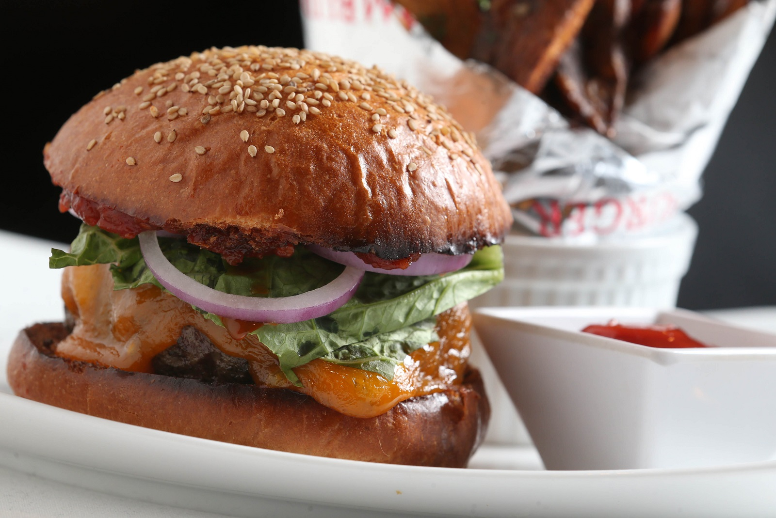Oliver's Restaurant's burger is 10-ounce certified angus beef prime, smoked cheddar, lettuce, red onion and Spanish tomato jam. The fries come with a smoked tomato ketchup. (Sharon Cantillon/Buffalo News)