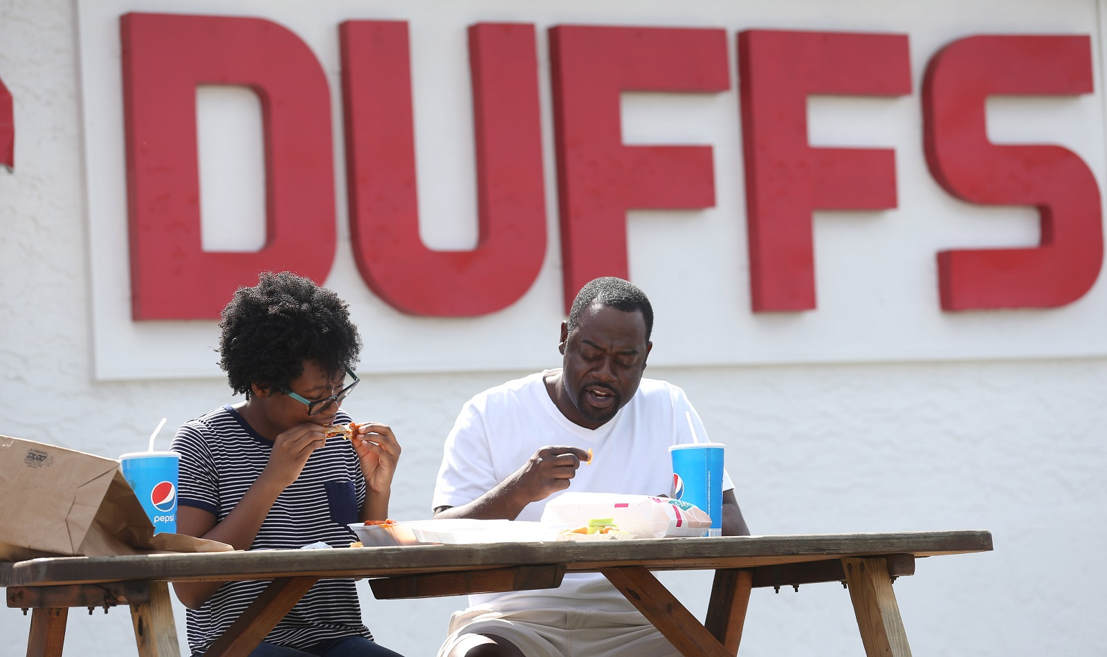 Geuka Amusa, right, and his daughter Isis, of Atlanta, drove straight from the airport to have lunch at Duff's on the way to Niagara Falls. (Sharon Cantillon/Buffalo News)