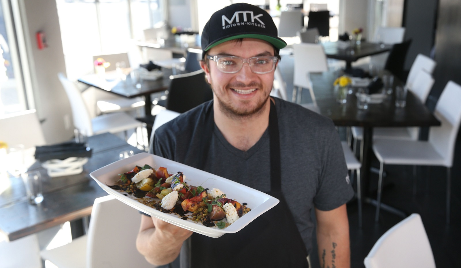 Midtown Kitchen executive chef Adrian Bylewski presents the grilled peach and tomato salad in September 2016. (Sharon Cantillon/Buffalo News)