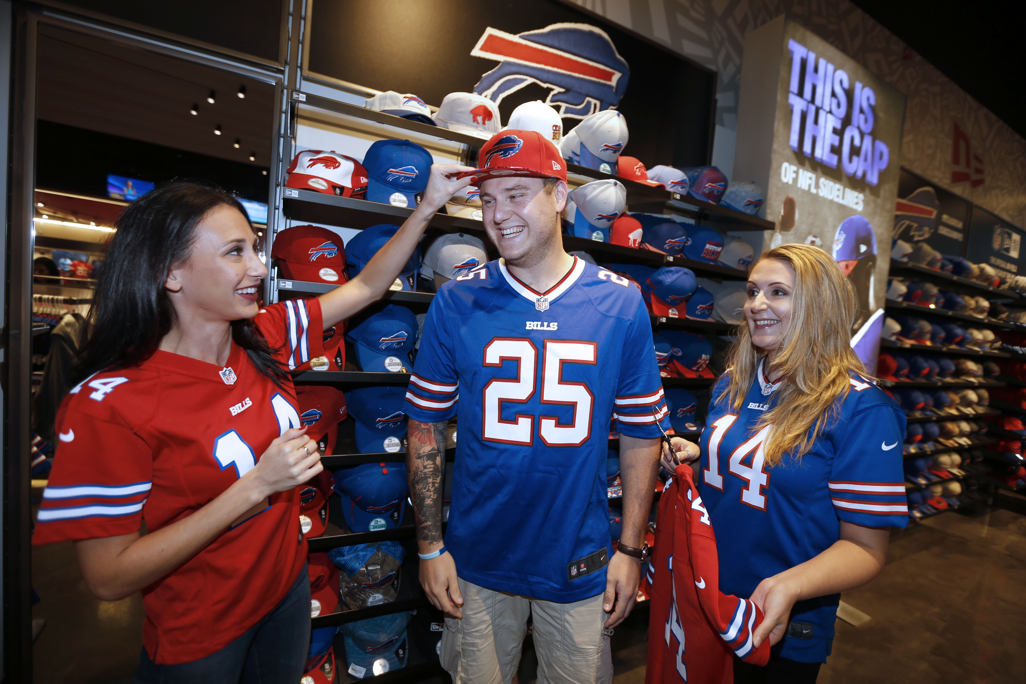 Inside the Bills Store at New Era Field where the Buffalo Bills play are, Matt Wild, center, and his wife Claire Wild, right, from Helston, Cornwall, England and their host Jenna Scavone, left, of Orchard Park on  Tuesday.  (Robert Kirkham/Buffalo News)