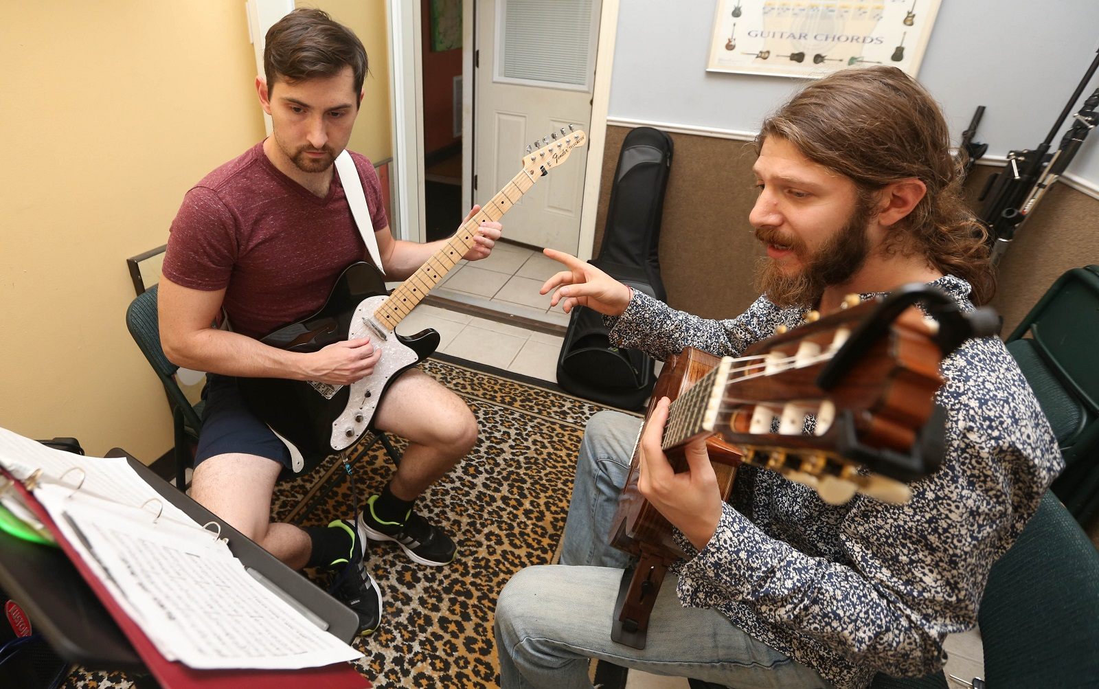 Drew Azzinaro, right, is the director of Daily Planet's music school. He gives a guitar lesson to Tom Graber of Buffalo. They have three rooms for individual lessons. (Sharon Cantillon/Buffalo News)