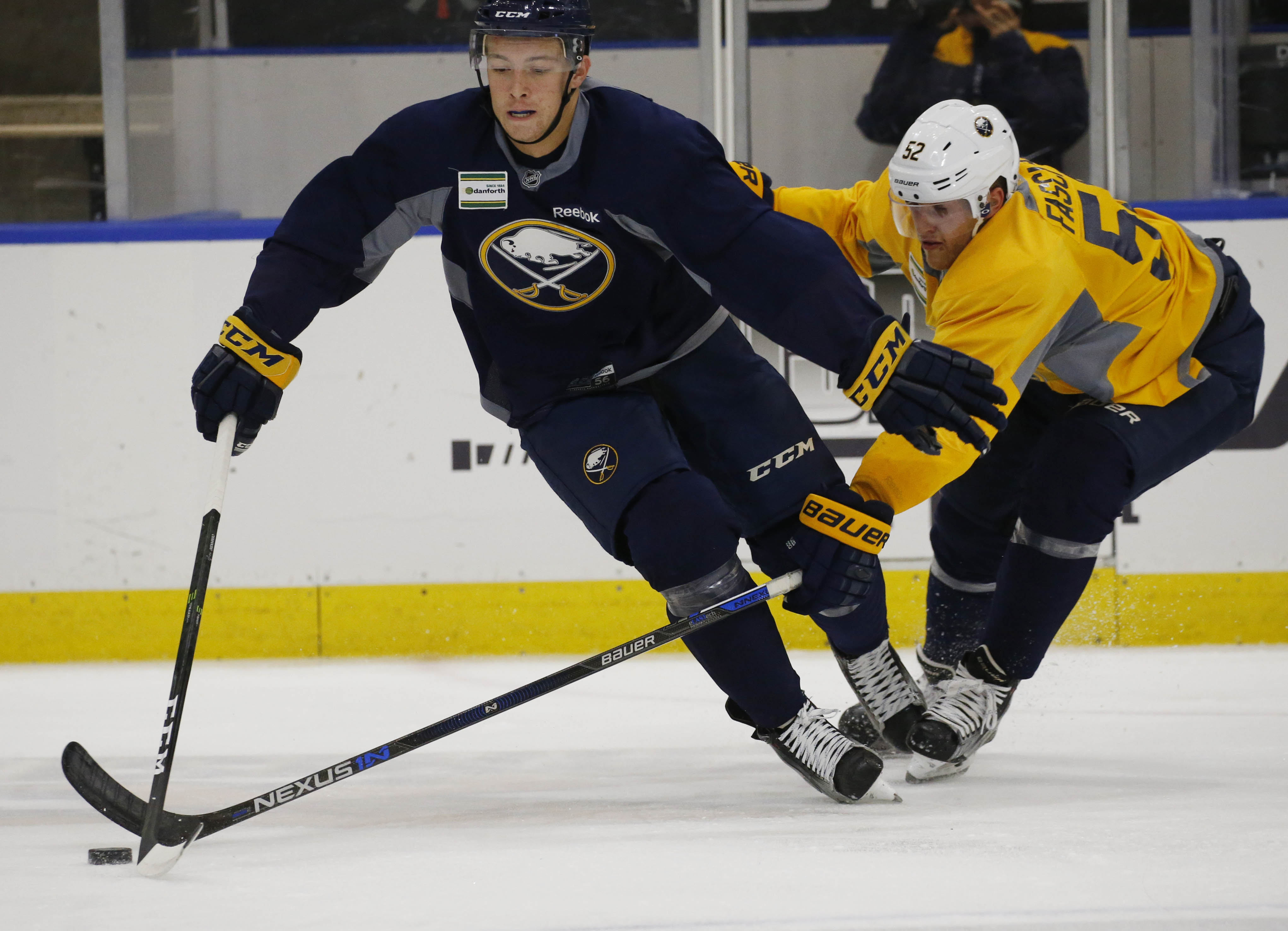 Austin Osmanski (51) gets the puck poke-checked away by Hudson Fasching (52) during the opening day of Buffalo Sabres training camp at HarborCenter.  (Derek Gee/Buffalo News)