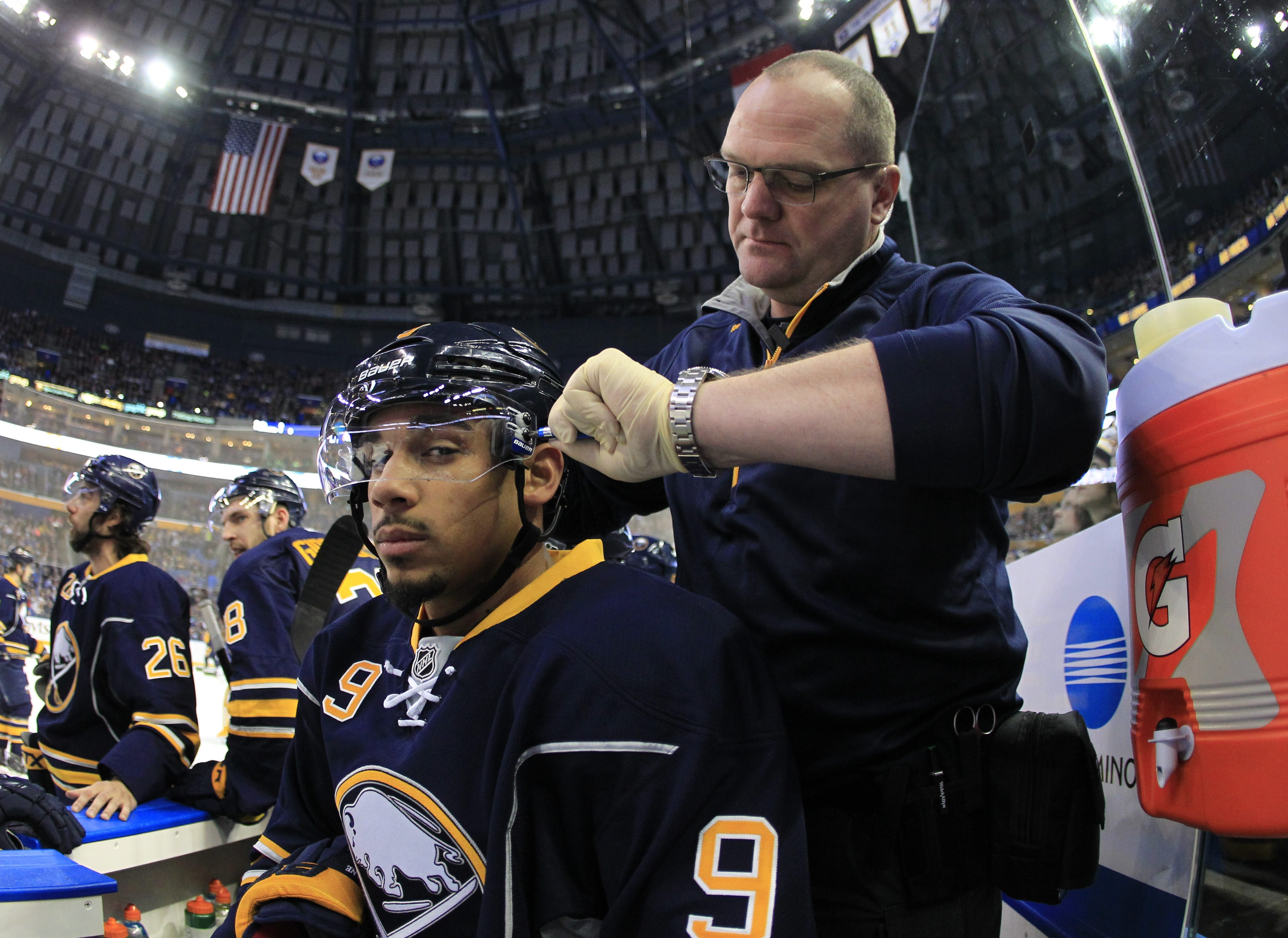Buffalo Sabres  trainer Tim Macre adjusts the helmet of Evander Kane on Feb. 14. Macre has left the team to join a local running company.