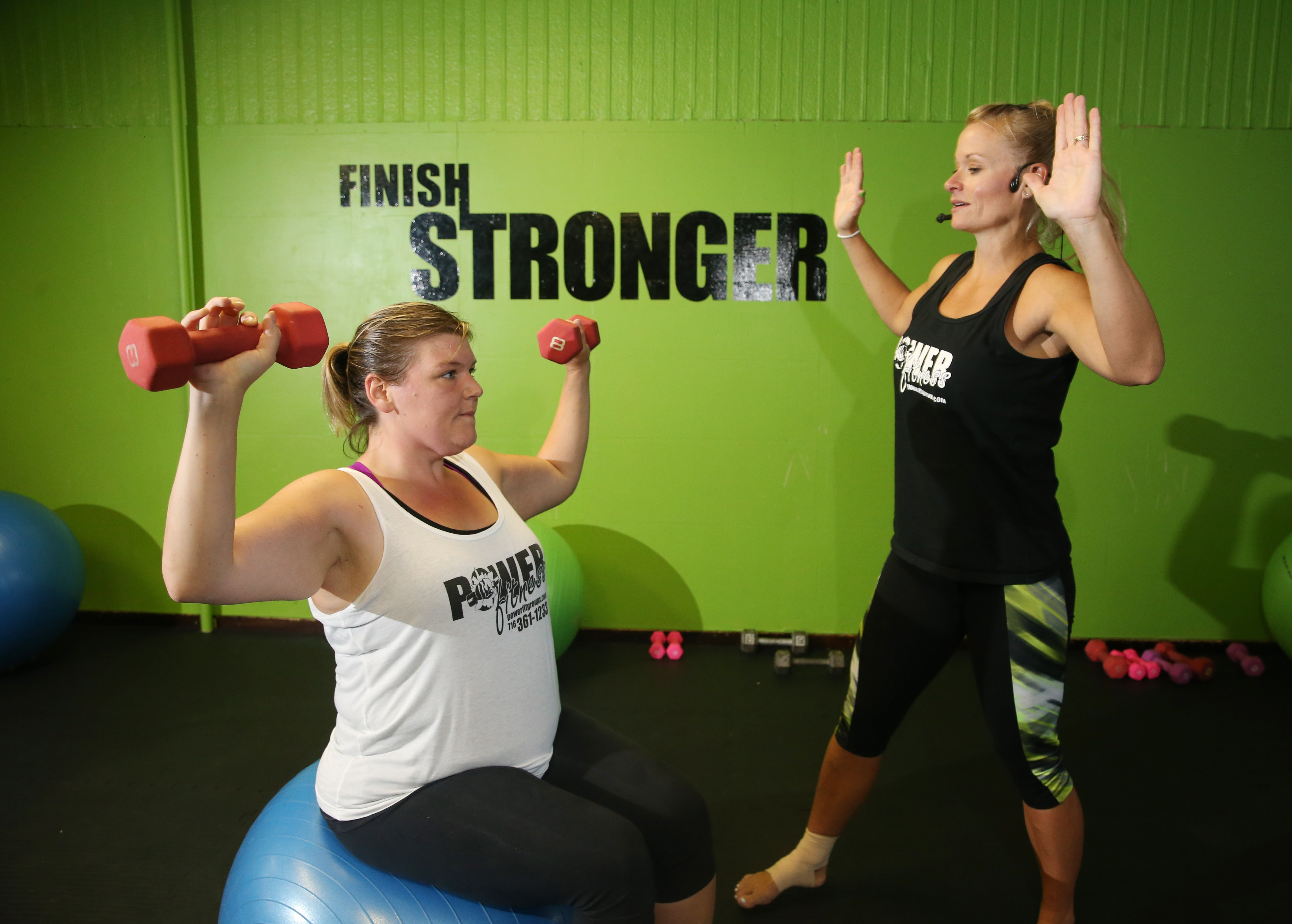 Sarah Coburn, owner of Power Fitness Group Exercise Studio in North Tonawanda, works with Marissa Nicholson, of Cambria, who started her weight-loss journey during the fall of 2013 and has lost 73 pounds since. (Sharon Cantillon/Buffalo News)