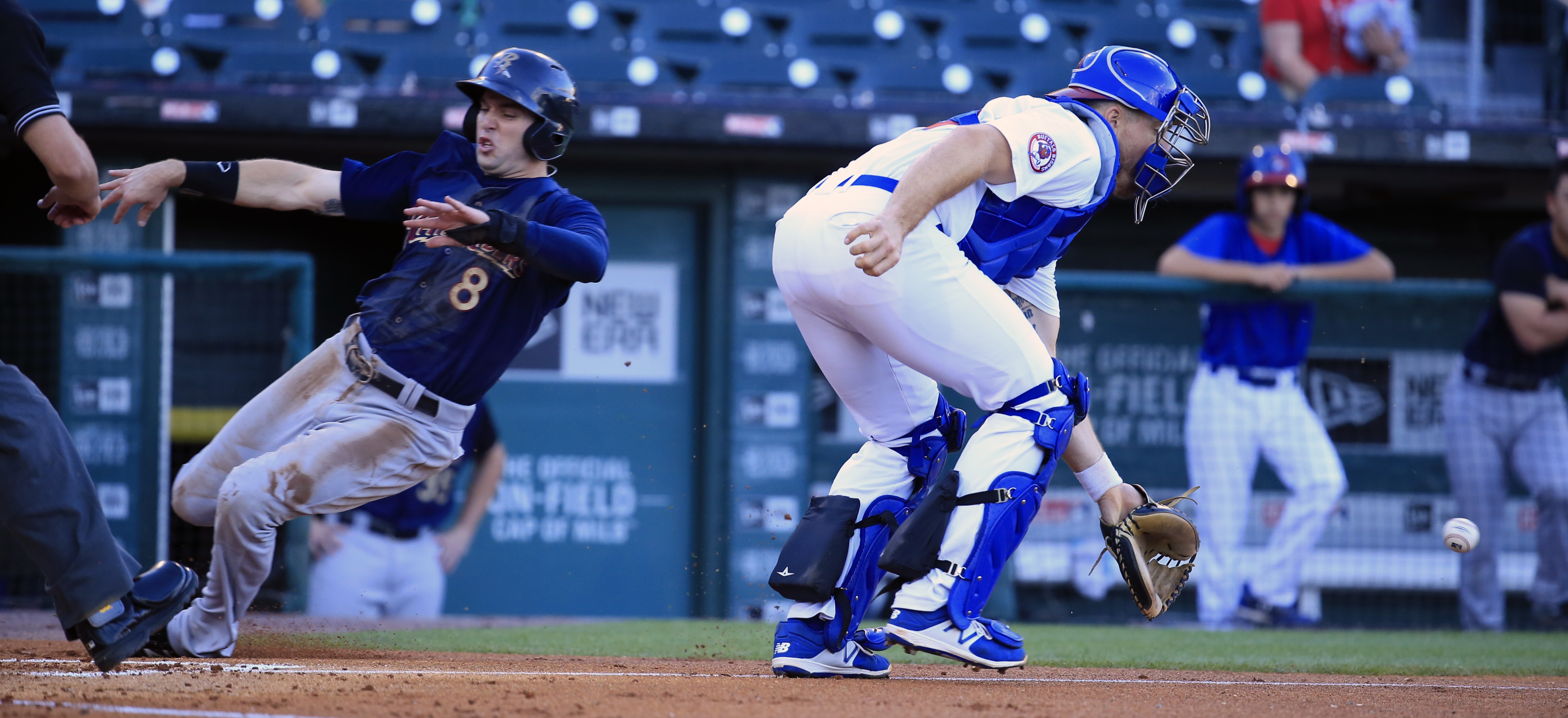 Scranton/Wilkes-Barre's Jake Cave slides past Buffalo Bisons catcher Erik Kratz to score during Thursday's game at Coca-Cola Field.