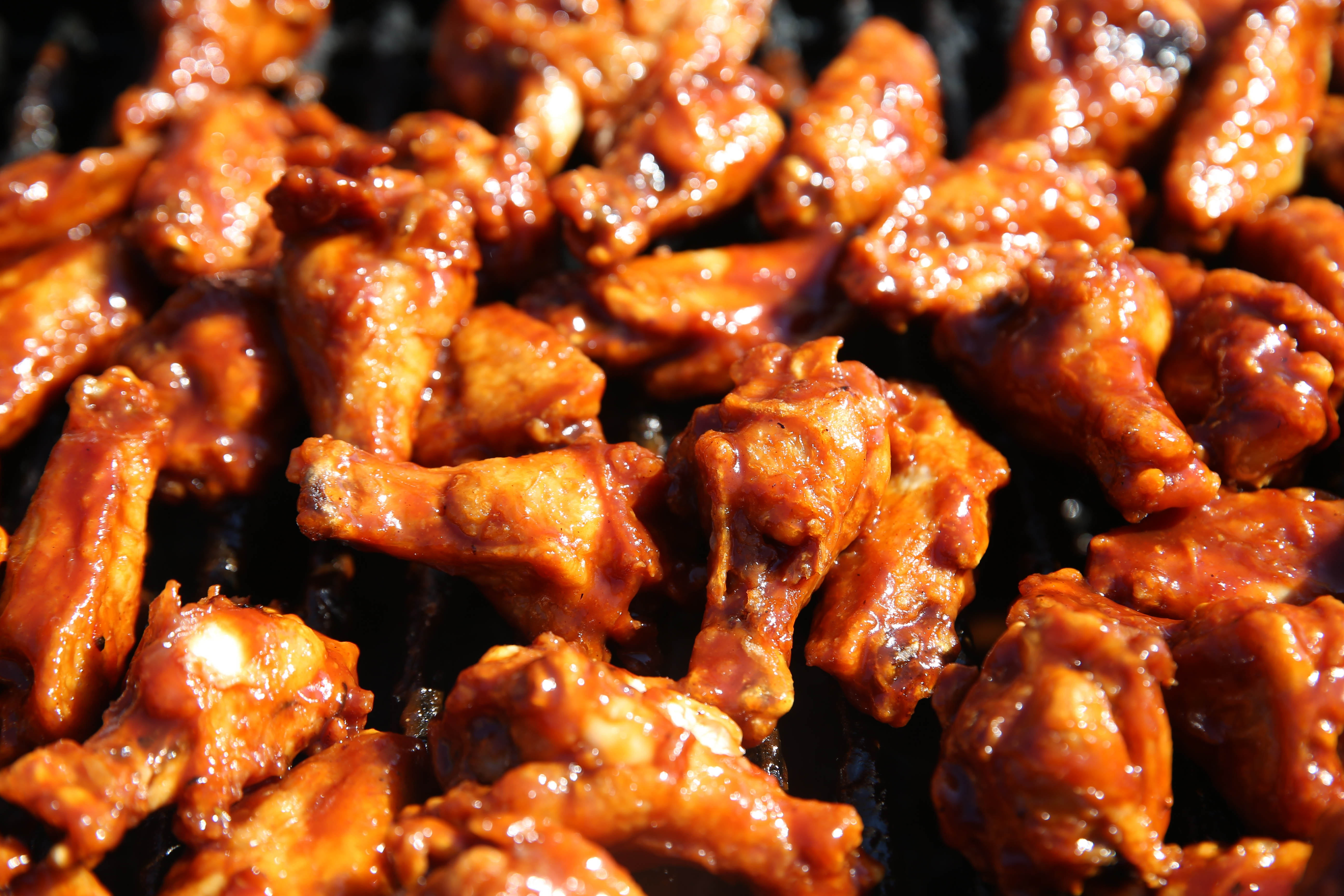 Tony Principato of Duffs sauces and grill their specialty Dr. Pepper BBQ wings.(Sharon Cantillon/Buffalo News)