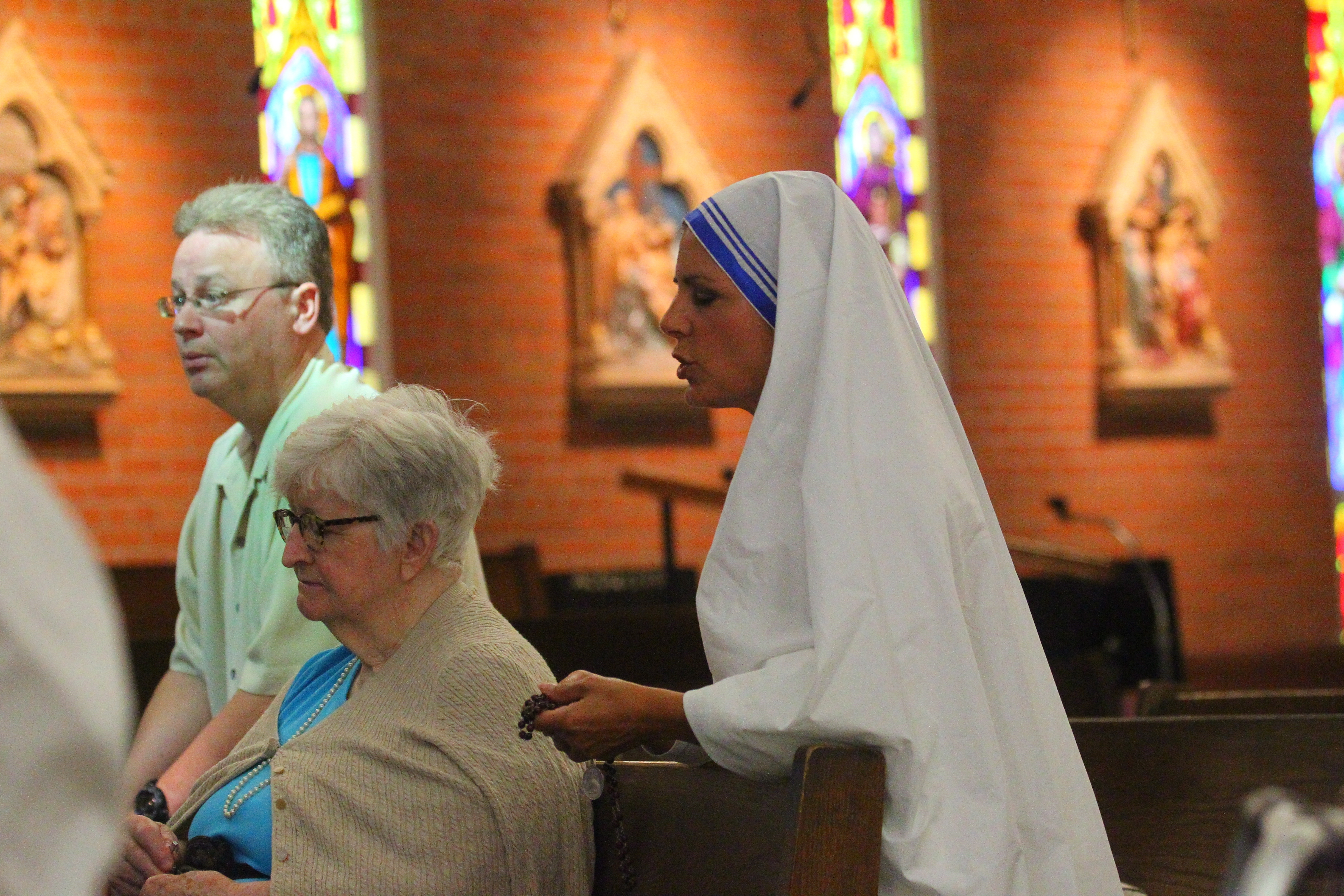 Dawn Iacono, right, a member of the staff at St. Leo the Great Church in Amherst, wears a replica of Saint Theresa of Calcutta's sari and veil as fellow Catholics pray in the church on Sunday. Below, a display in the church atrium honors the new saint.