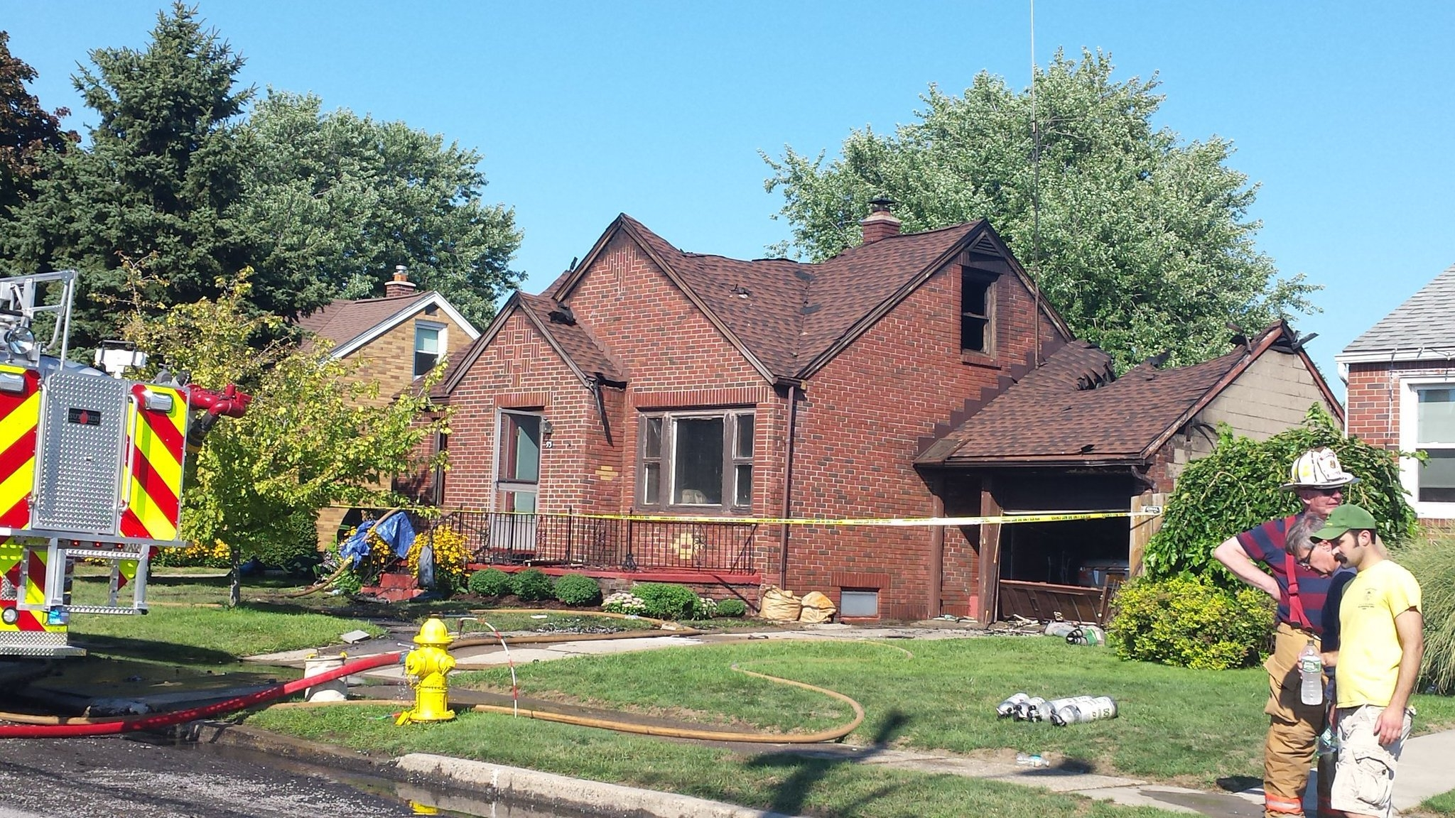 Firefighters rope off the burned home on Peoria Avenue in Cheektowaga. (Jonathan Epstein/Buffalo News)