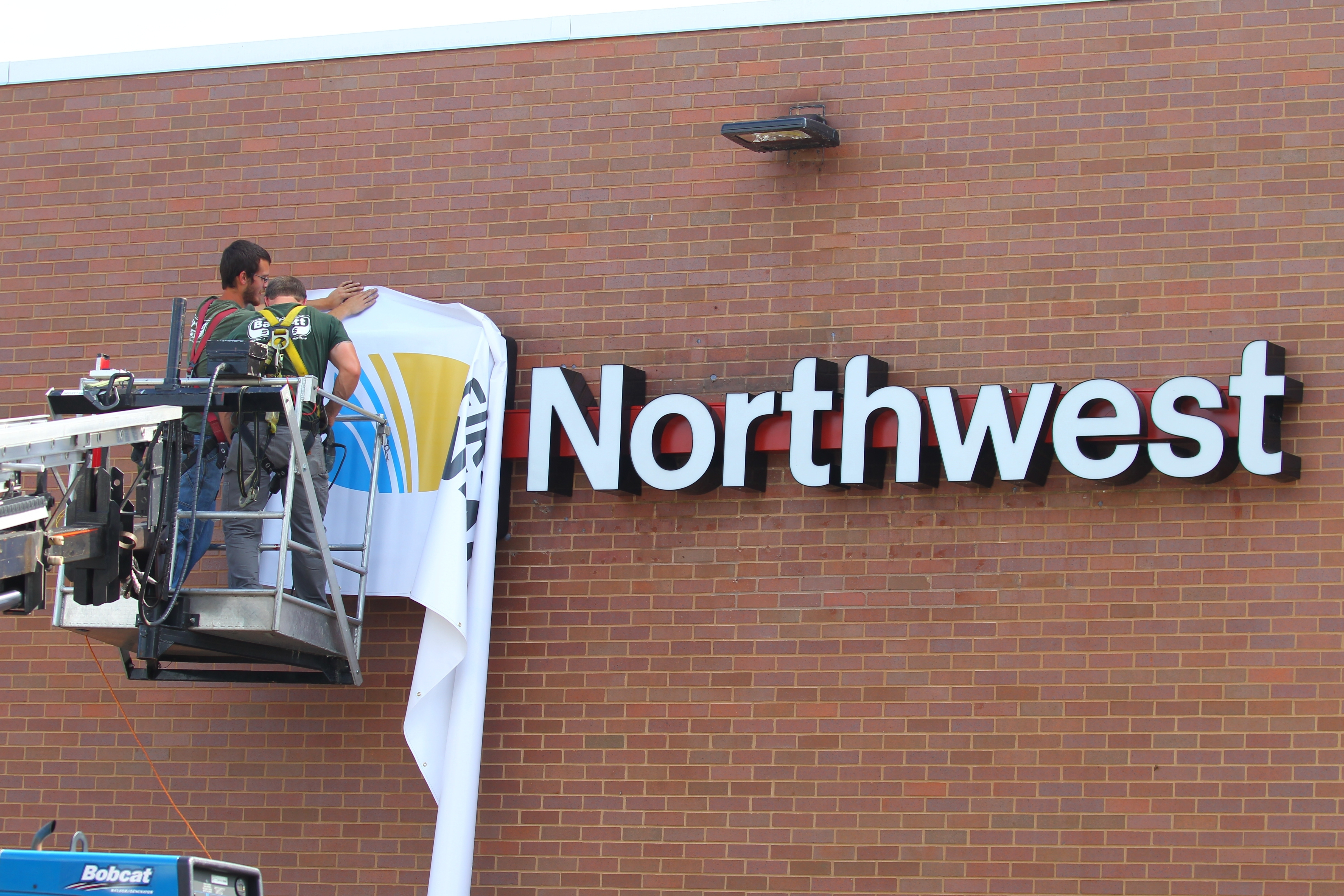 Workers install an interim First Niagara banner at  an already rebranded Northwest Bank at 690  Kenmore Ave.