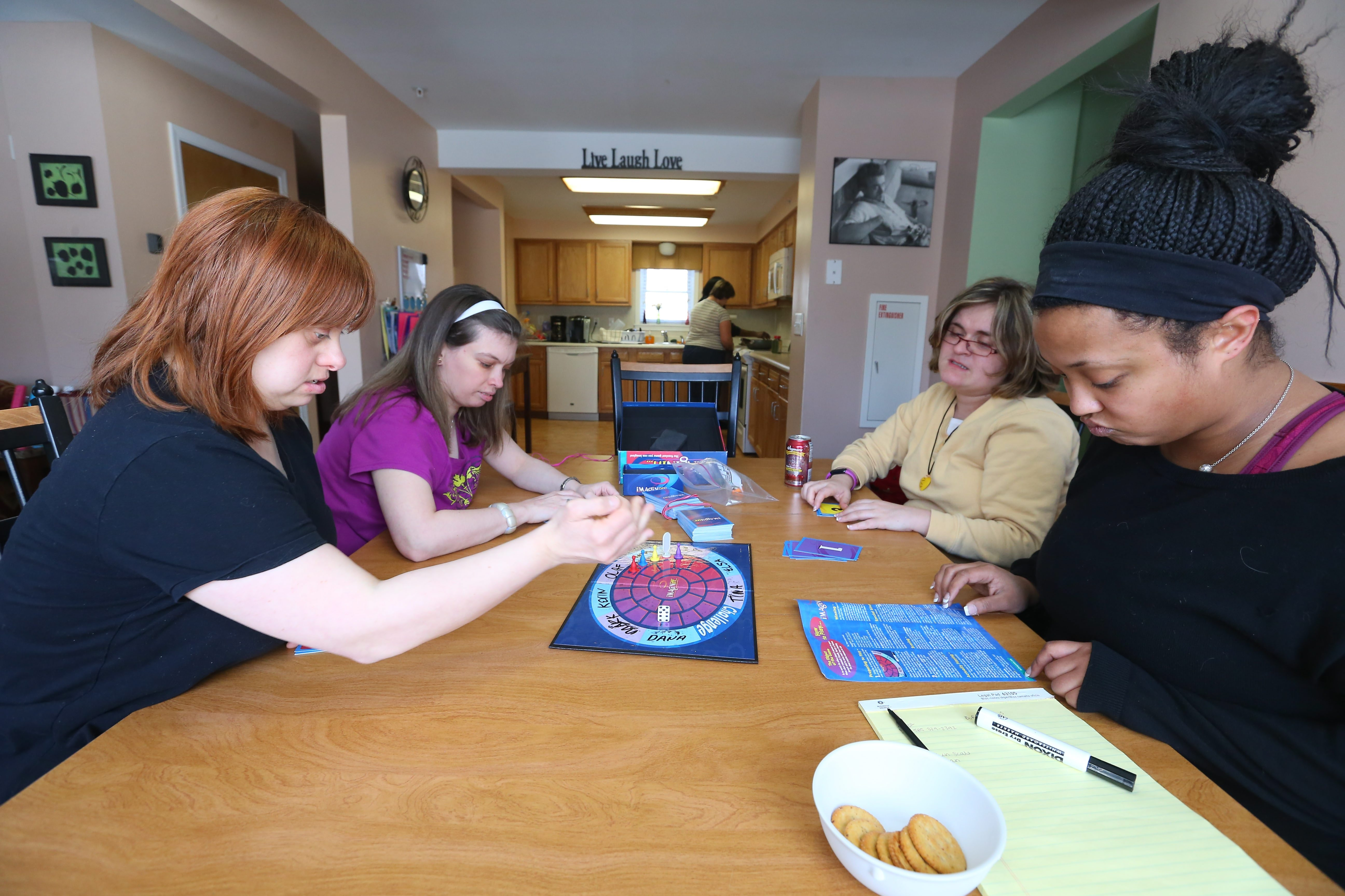 Three residents and their senior residential supervisor Fatima Johnson, right, play a game at their group home in Amherst last year. (Mark Mulville/Buffalo News)