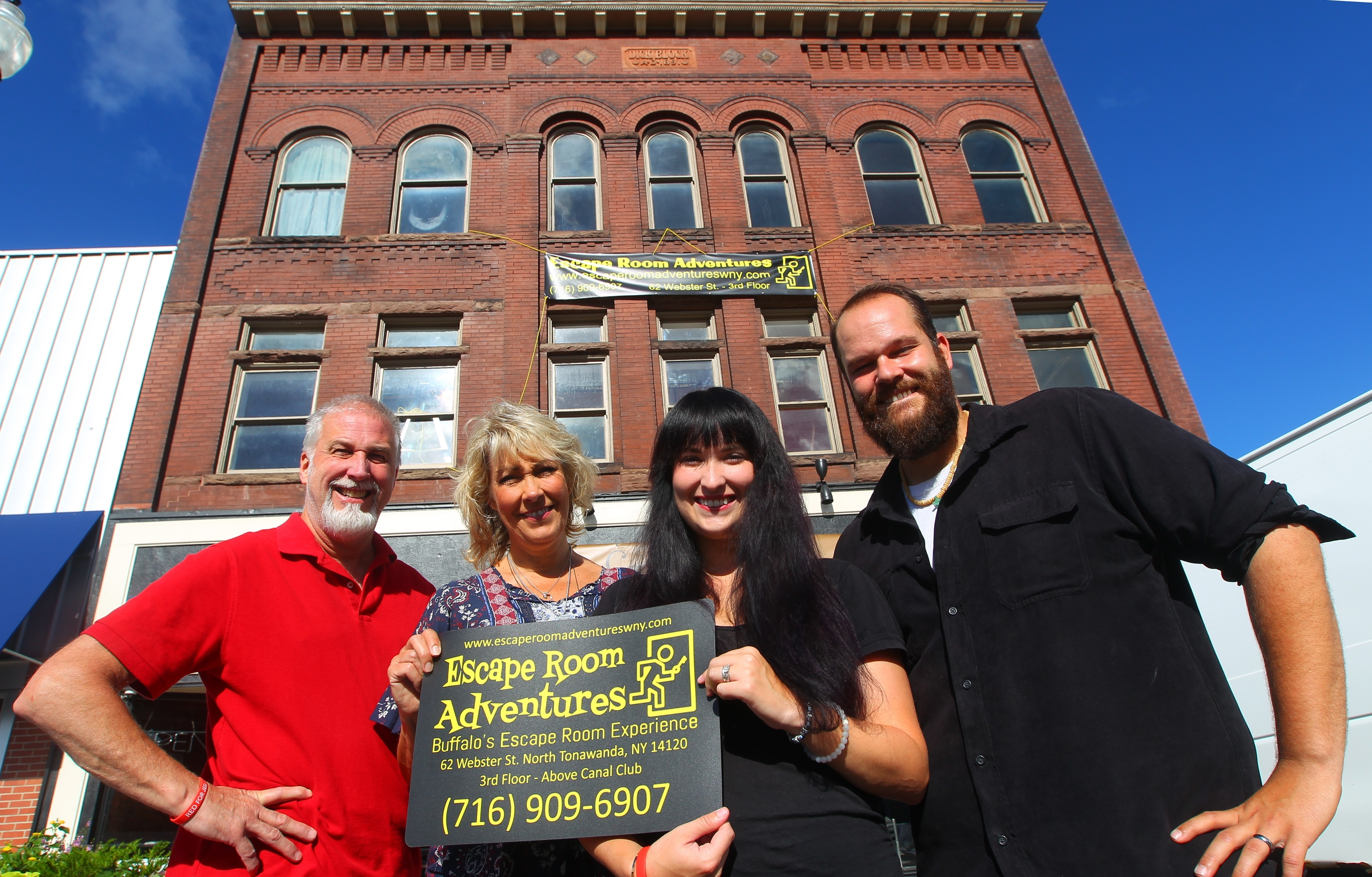 Mark Woomer and his wife Carolyn, daughter Amanda Limpert, and Amanda's husband Adam in front of their family business Escape Room Adventures WNY on the third floor at 62 Webster St., in North Tonawanda, N.Y. on Thursday Sept. 1, 2016.  (John Hickey/North Tonawanda News)