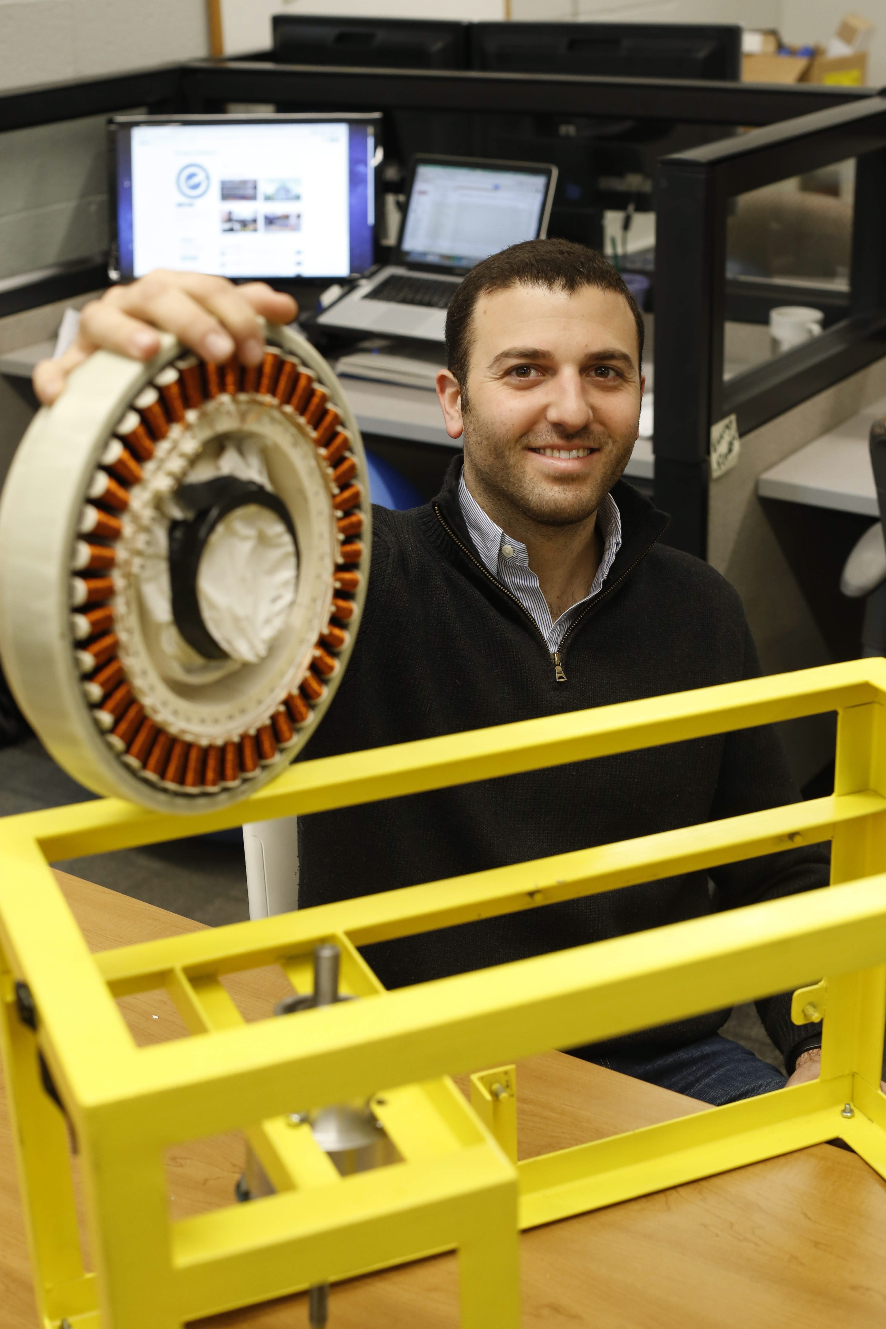 Daniel Shani, founder and CEO of Energy Intelligence, a startup company developing a device which uses the energy of passing cars (as they drive over a pressure sensitive pad or series of pads on the road) to create electricity, in his workspace at 43 North, Wednesday, March 23, 2016.  He's holding a generator used to power a prototype device and the frame used in testing and development.  (Derek Gee/Buffalo News)