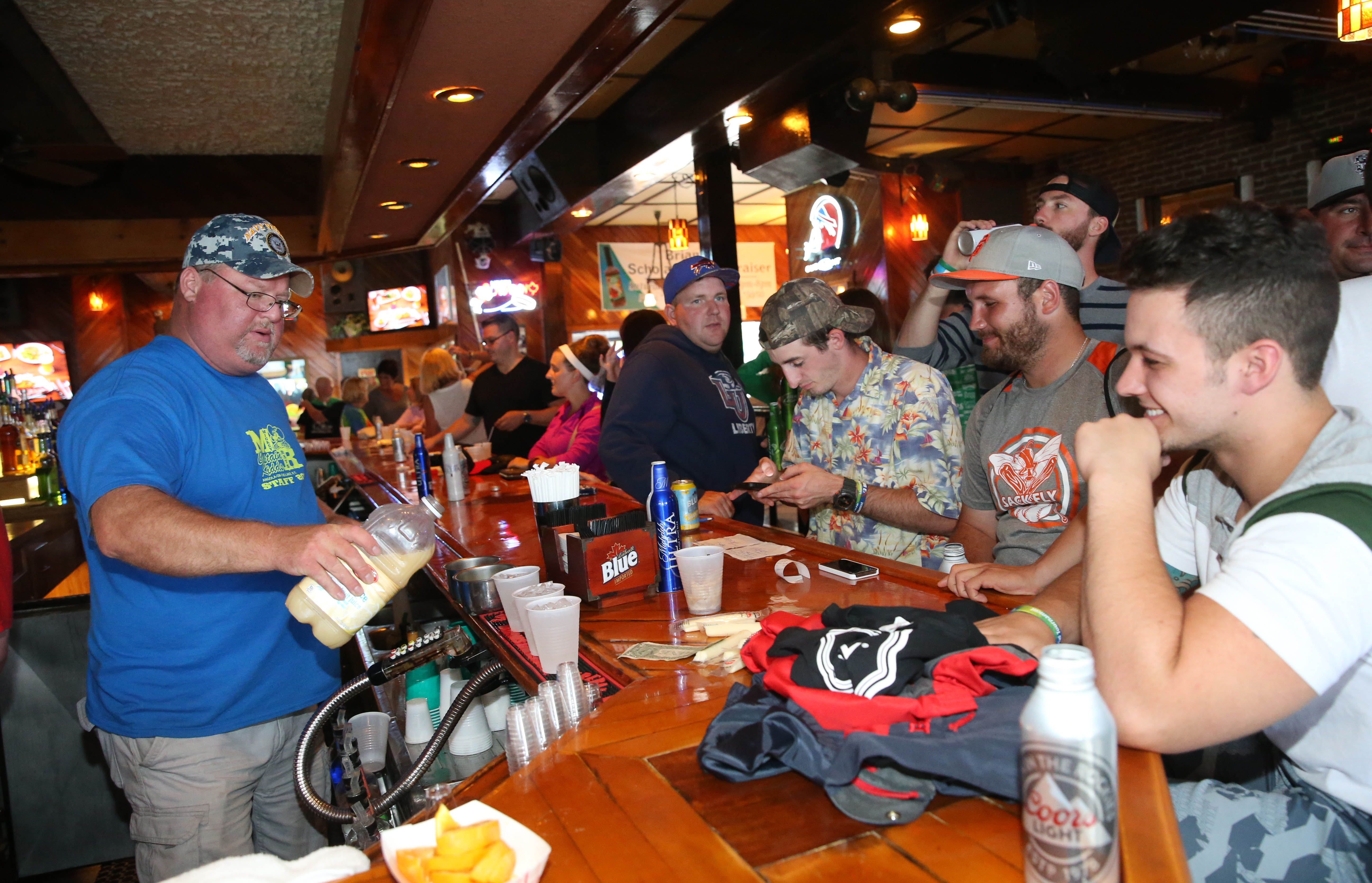 Greg Siwiec, pours drinks at Captain Kidd's in Angola Saturday, before a planned end-of-summer party later that night at the popular beach bar, which includes Mickey Rats.