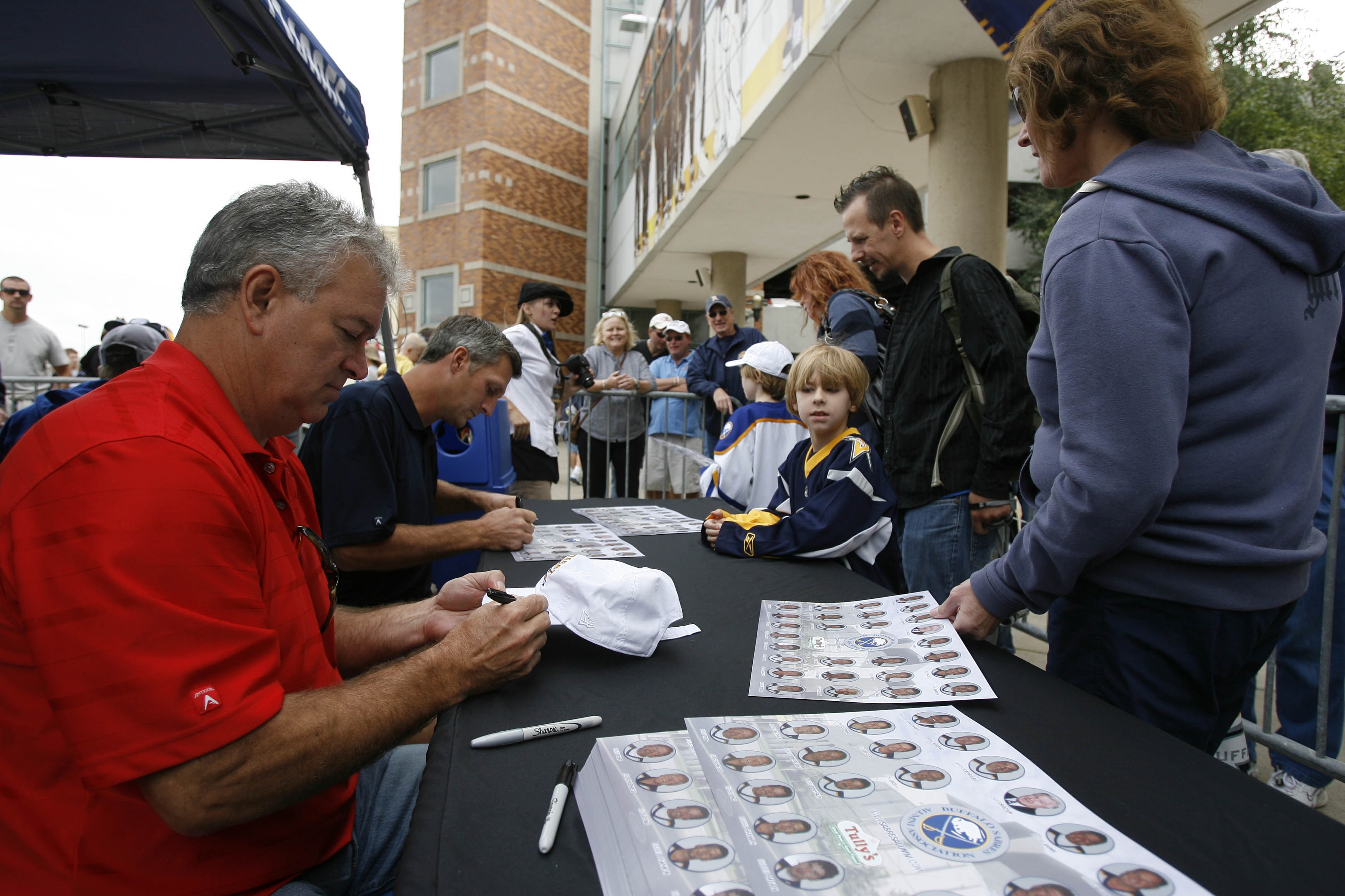 Sabres' Alumni Richie Dunn, left, and Darryl Shannon sign autographs for fans during Puck Drop 2010 at the HSBC Arena.