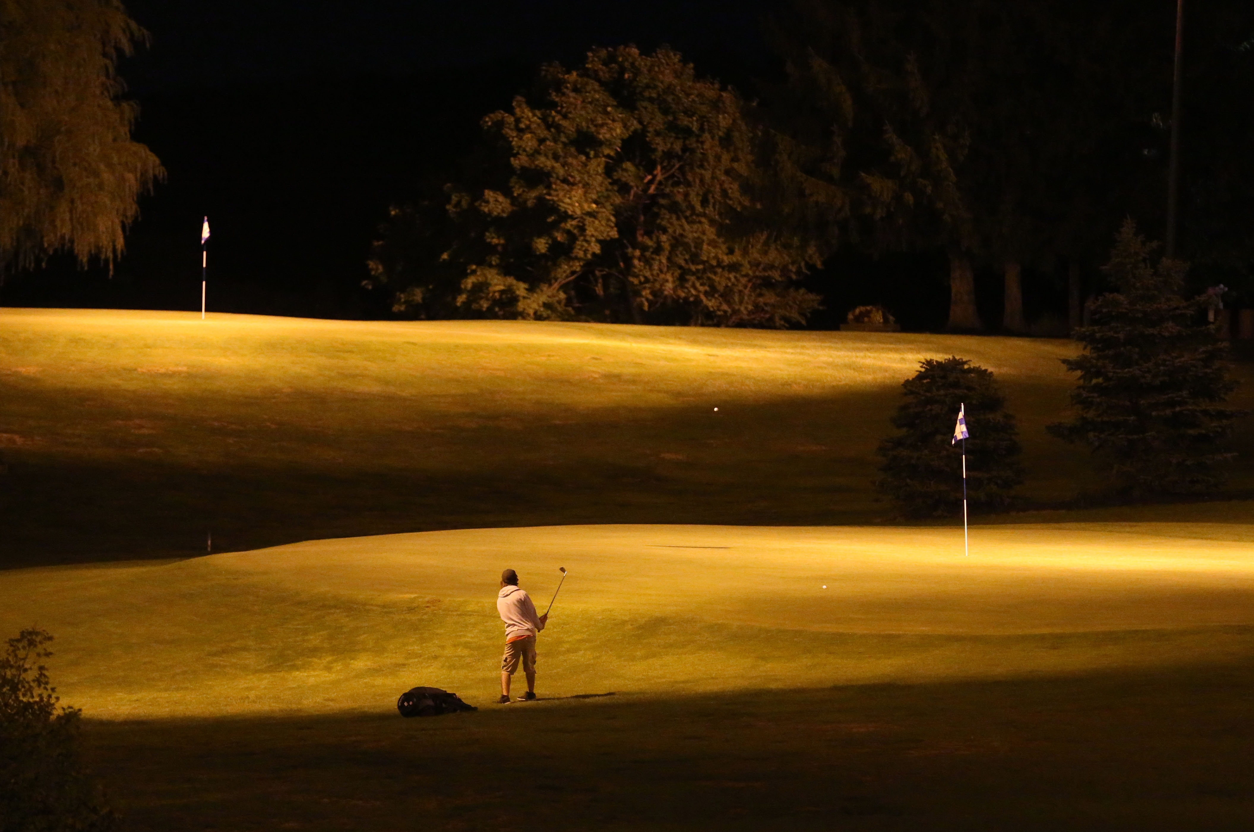 Night moves: Zach Lembke chips onto the 10th green during a recent round at Bob-O-Link Golf Club on Transit Road in Orchard Park, which also offers glow-in-the-dark balls, below, for $10. The last tee time at the family-run operation is at 9:30 p.m., and there is also a snack bar with beer, wine and food available.  Photos by Sharon Cantillon/Buffalo News