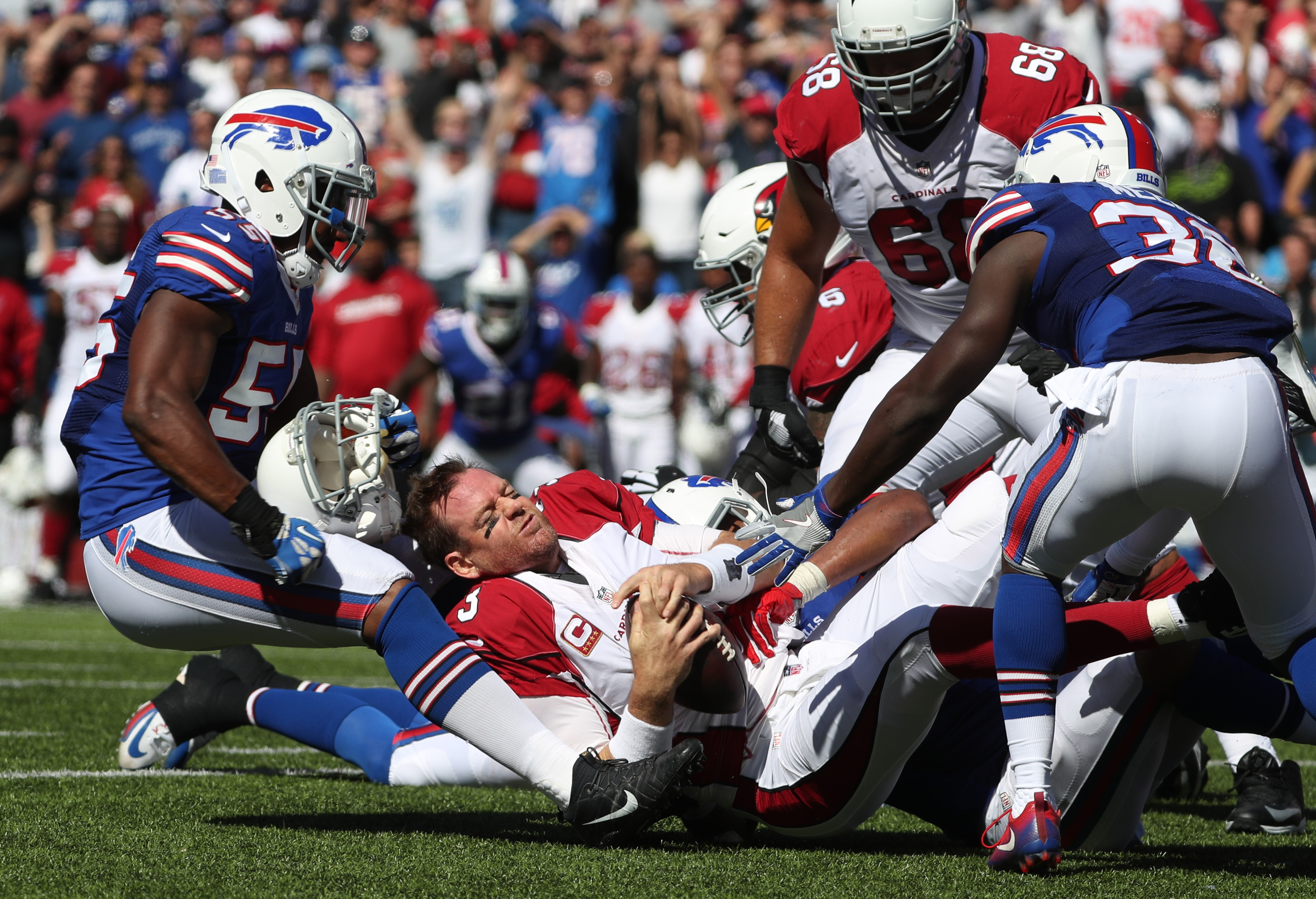 Carson Palmer has his helmet ripped off by Jerry Hughes during the second quarter. (James P. McCoy/Buffalo News)