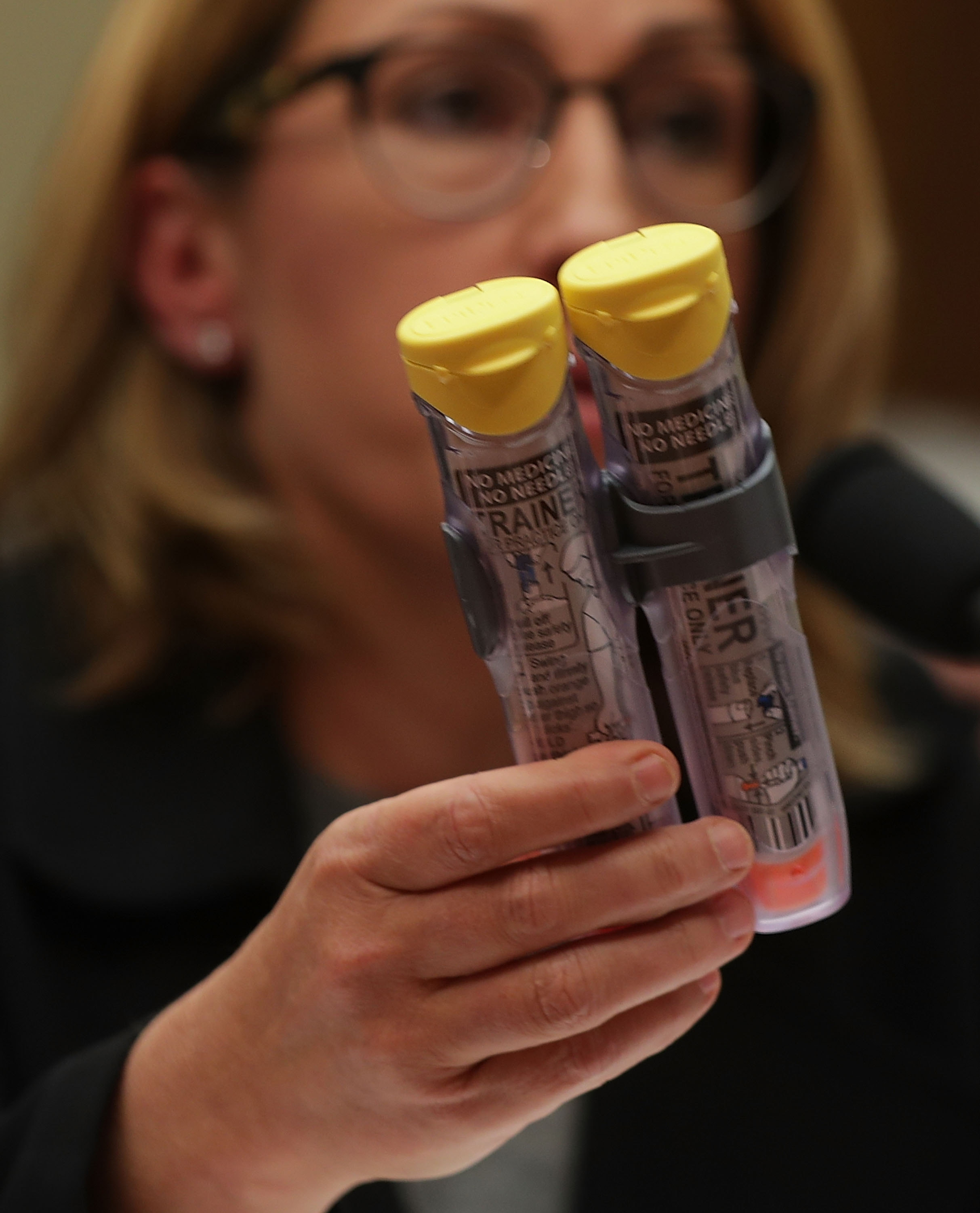 """WASHINGTON, DC - SEPTEMBER 21:  Mylan Inc. CEO Heather Bresch holds up a 2-pack of EpiPen as she testifies during a hearing before the House Oversight and Government Reform Committee September 21, 2016 on Capitol Hill in Washington, DC. The committee held a hearing on """"Reviewing the Rising Price of EpiPens.""""  (Photo by Alex Wong/Getty Images)"""