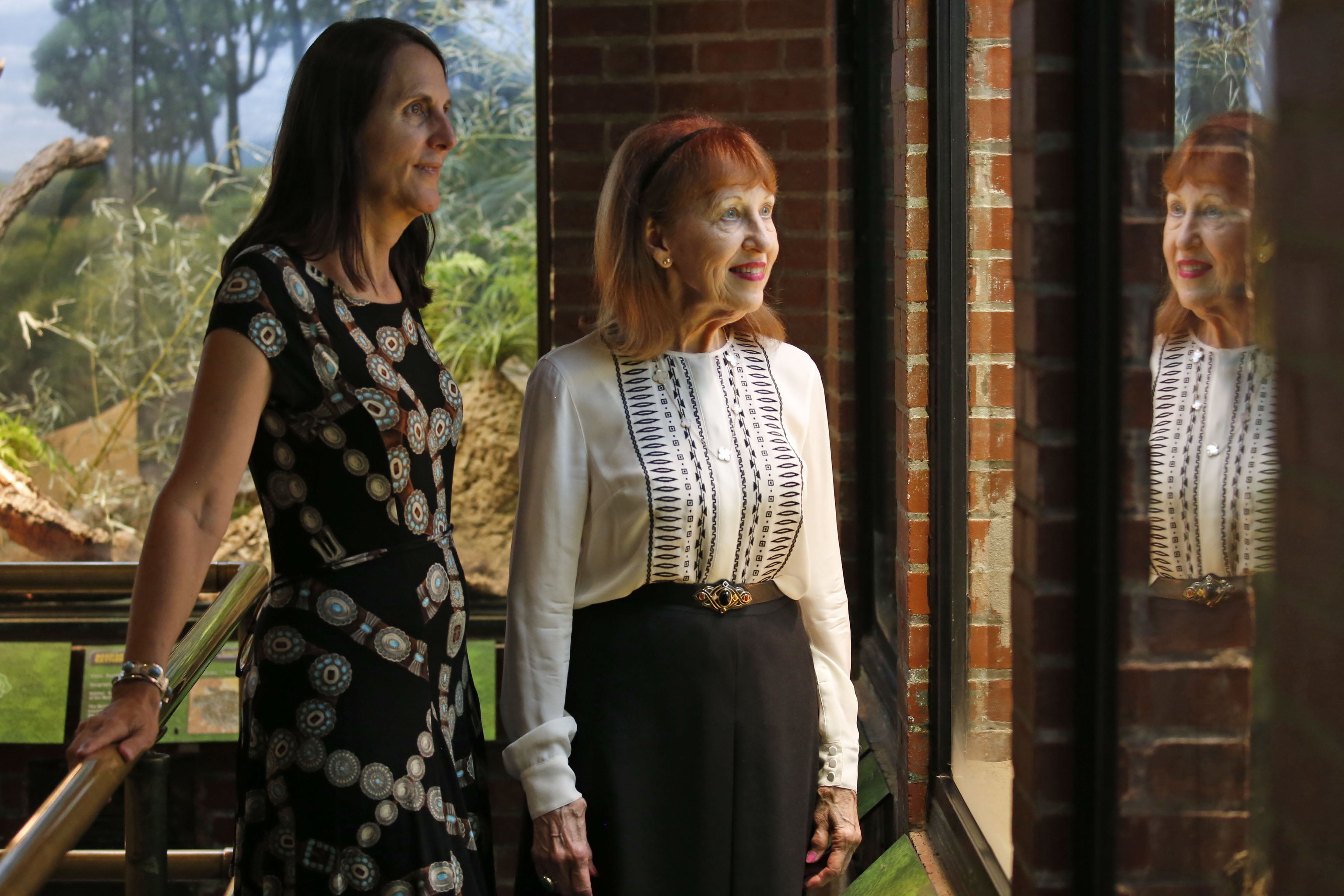 """Suzanne Perkins-Gordon, right, daughter of Marlin Perkins, a zoologist who ran the Buffalo Zoo before becoming the TV host of """"Wild Kingdom,"""" toured the exhibits Wednesday with a fan of her father, Zoo President Donna Fernandes."""