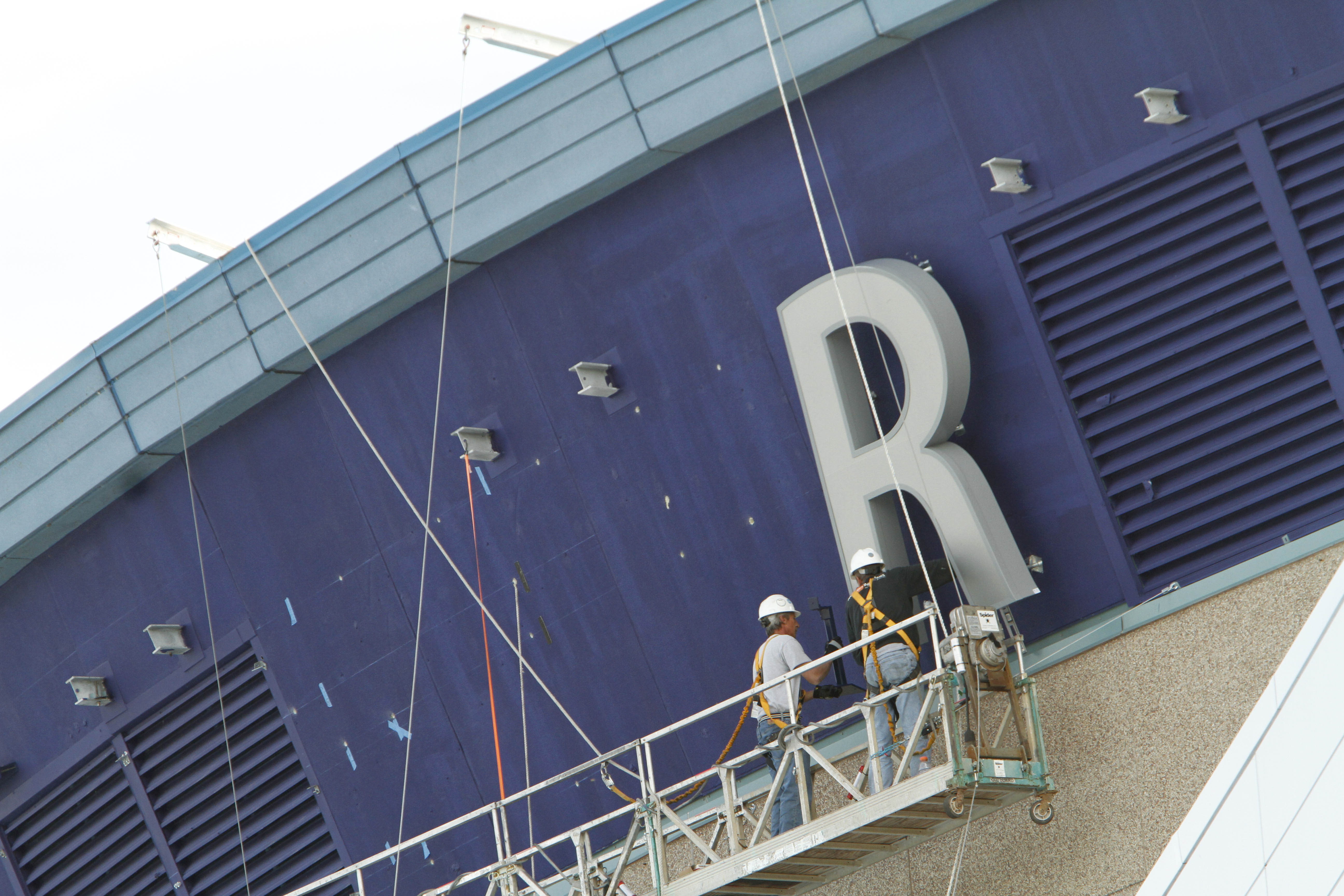 { STAND ALONE / PICTURE PAGE } Workers secure the first letter, an R which has been up since Tuesday, onto the roof of the recently renamed First Niagara Center on Thursday afternoon, Oct. 13, 2011. {Photo by Derek Gee / Buffalo News}