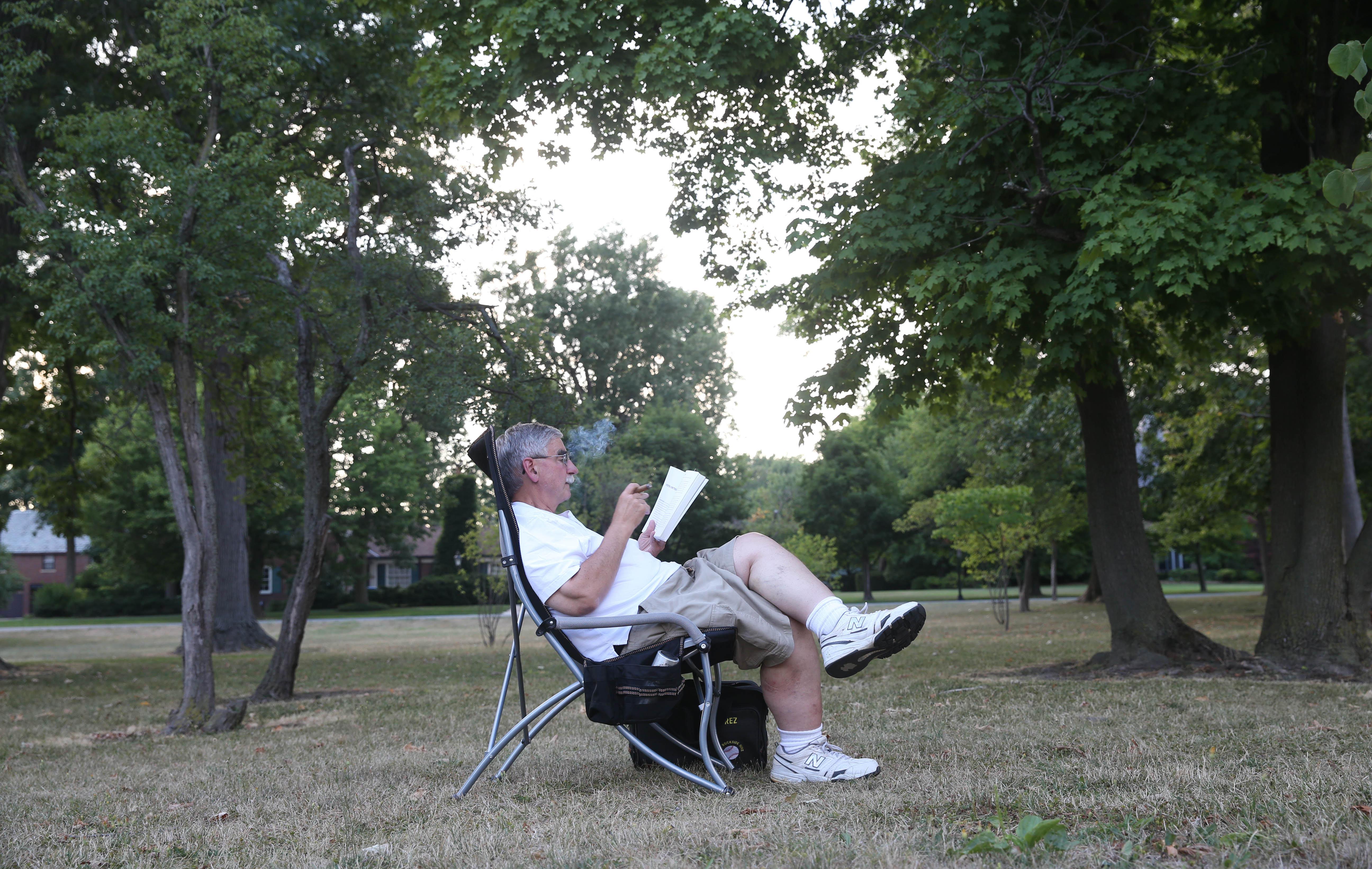 Zajac enjoys a book and a cigar in his portable chair. (Sharon Cantillon/Buffalo News)