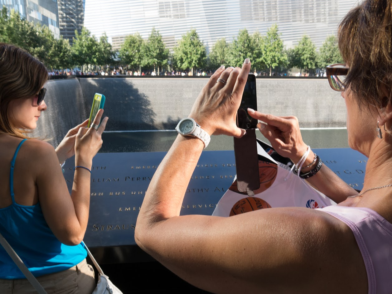 Bob Leonard spent a year capturing images of people taking photographs at the National Sept. 11 Memorial. While this image simply captures the general atmosphere, many of the photos show people mugging or laughing against a backdrop of the engraved names, of those who died. (Image courtesy Bob Leonard)