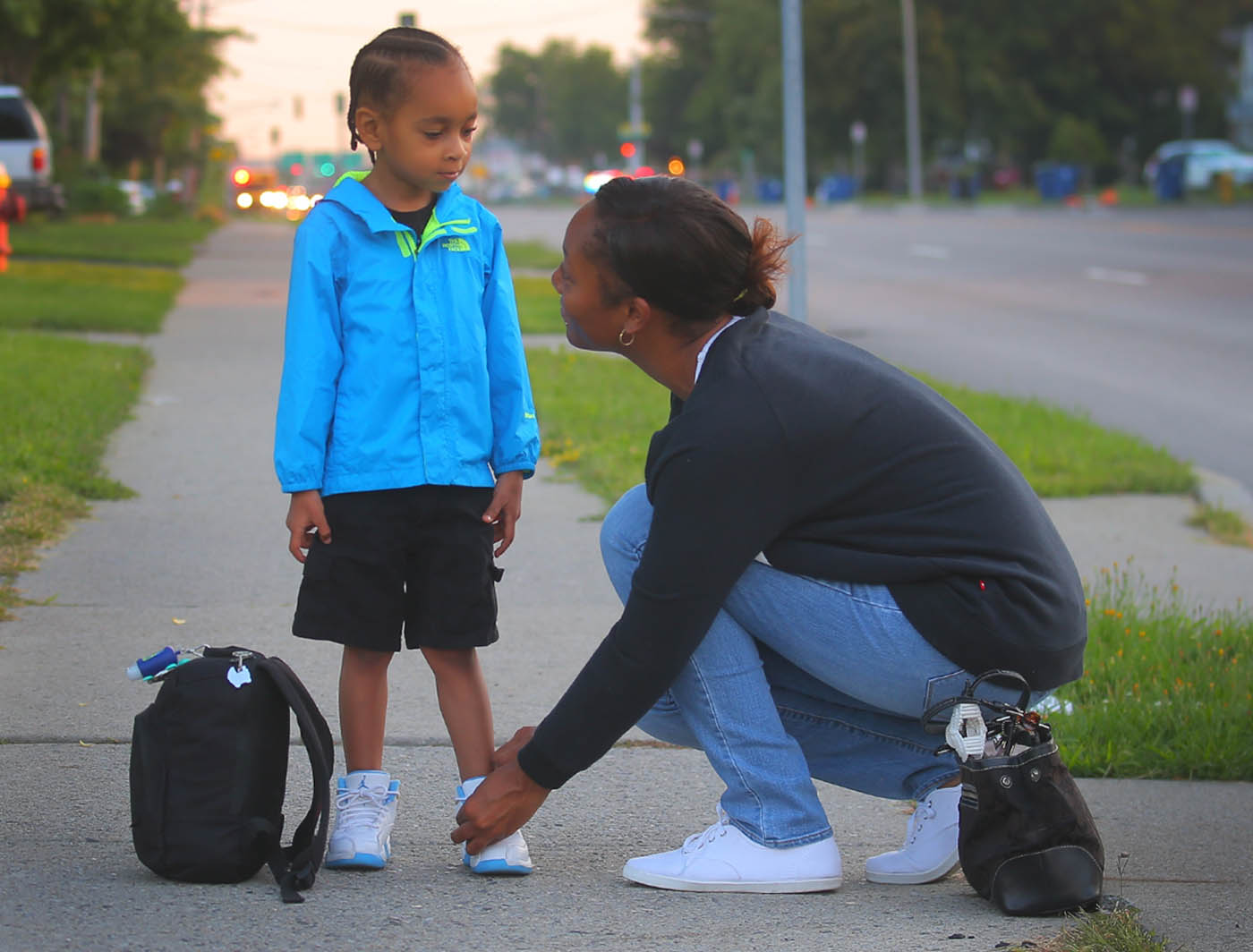 Natavia Siders, right, of Amherst, ties her sons shoe Namarien, 3, as they wait for the bus as Namarien heads to his first day of pre-k on the first day of school at the bus stop on Niagara Falls Blvd. in Town of Tonawanda, N.Y. on Tuesday Sept. 6, 2016. (John Hickey/Buffalo News)