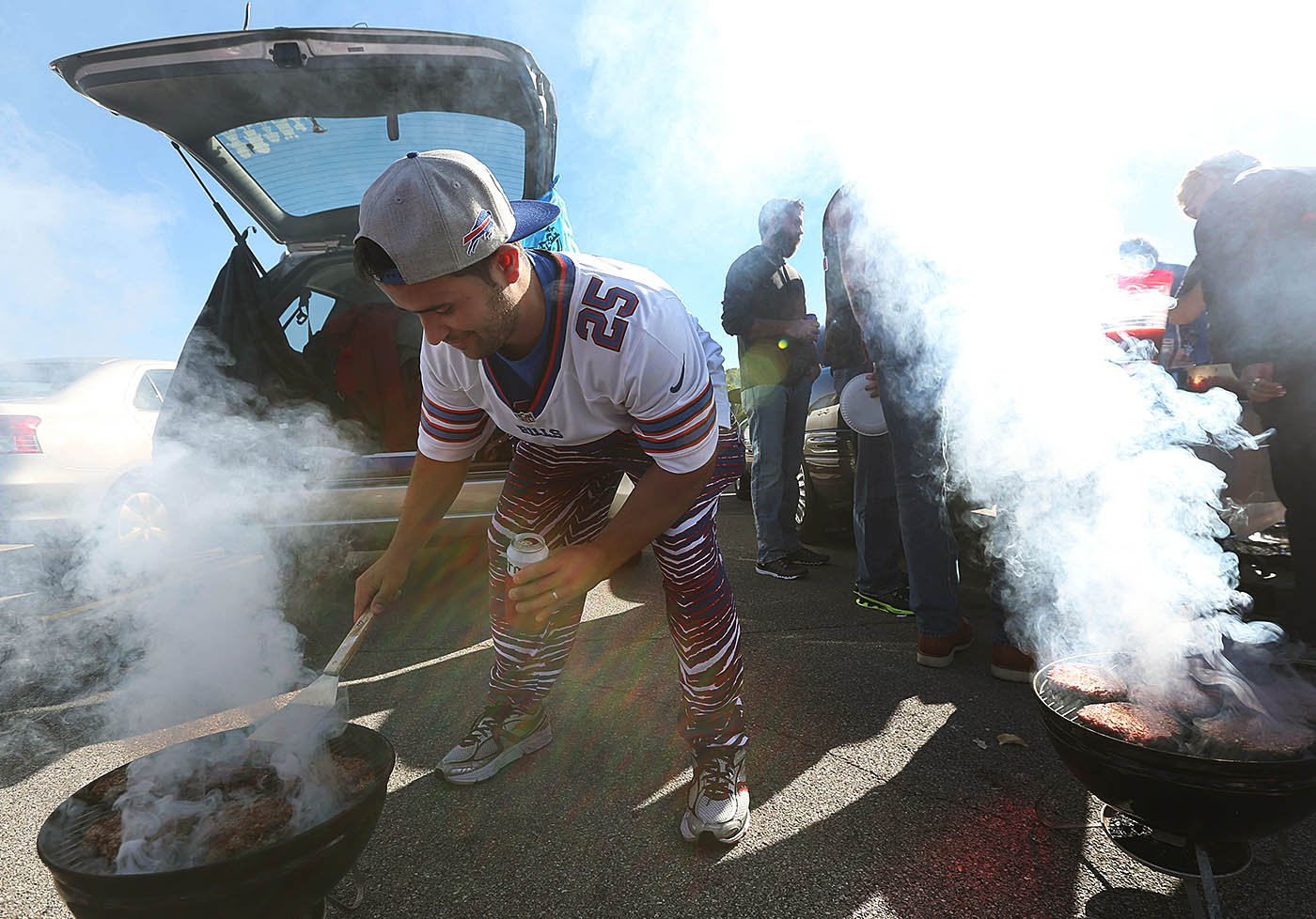 Tailgating before a Buffalo Bills game is an integral part of game-day fun around New Era Field, in Orchard Park.  Tailgaters bring an array of food and drink and visit with their neighbors prior to game time, Sunday, Sept. 25, 2016.  At 10 a.m. tailgating is in full swing.  Jeffrey Manca of West Seneca mans two grills filled with burgers.  He's a season ticket holder.  His dad began buying season tickets in 1966. (Sharon Cantillon/Buffalo News)