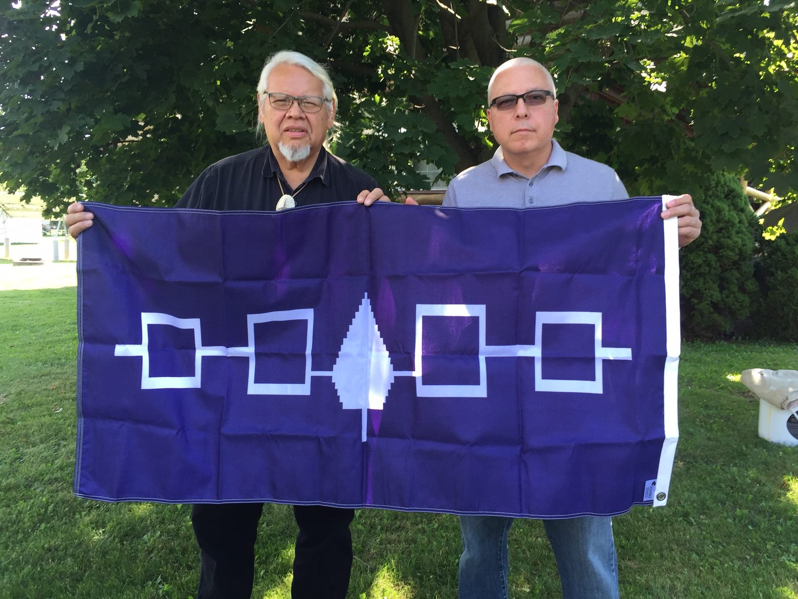 Rick Hill and Tim Johnson with the flag of the Six Nations: Hill, a Tuscorara, and Johnson, a Mohawk, were deeply involved with the genesis of what's become an iconic symbol of the Haudenosaunee, or Iroquois Confederacy. (Image courtesy Tim Johnson)