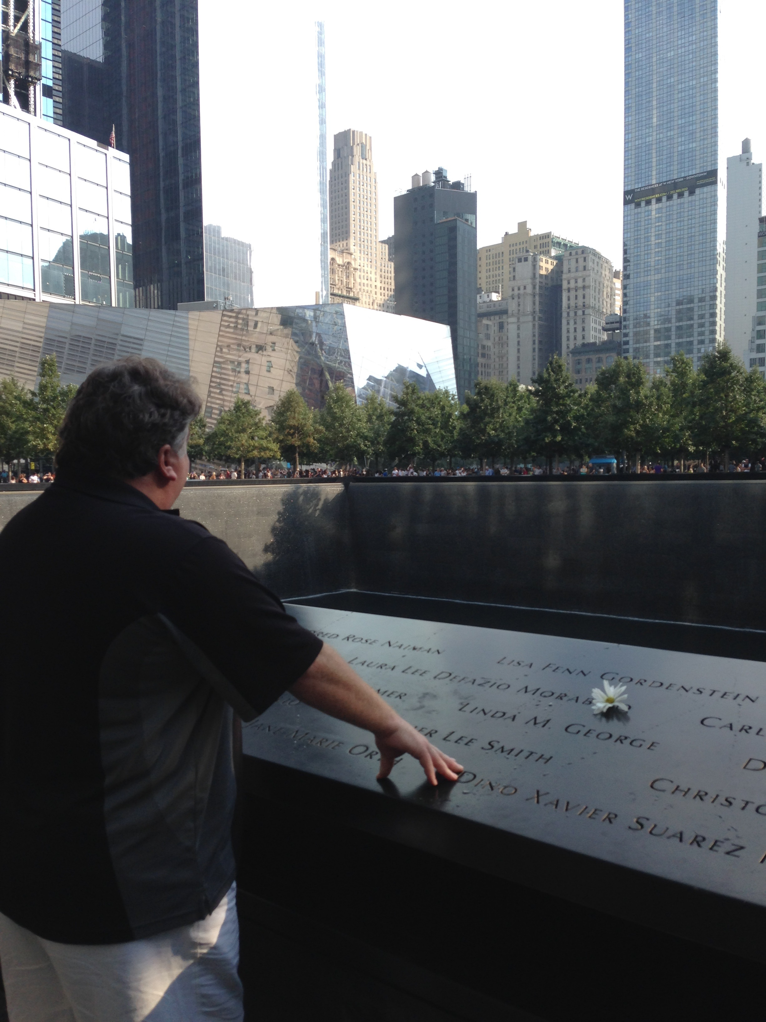 Mark Morabito, Saturday, above the name of his wife, Laura Lee DeFazio Morabito, National Sept. 11 Memorial, Manhattan. Morabito said he was moved to discover a stranger left a flower, by his wife's name. (Photo courtesy Morabito family)