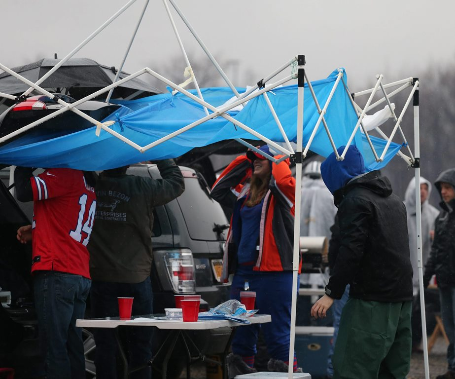 Bills fans tailgate in the pouring rain at Ralph Wilson Stadium at a game last season. (James P. McCoy/ Buffalo News file photo)