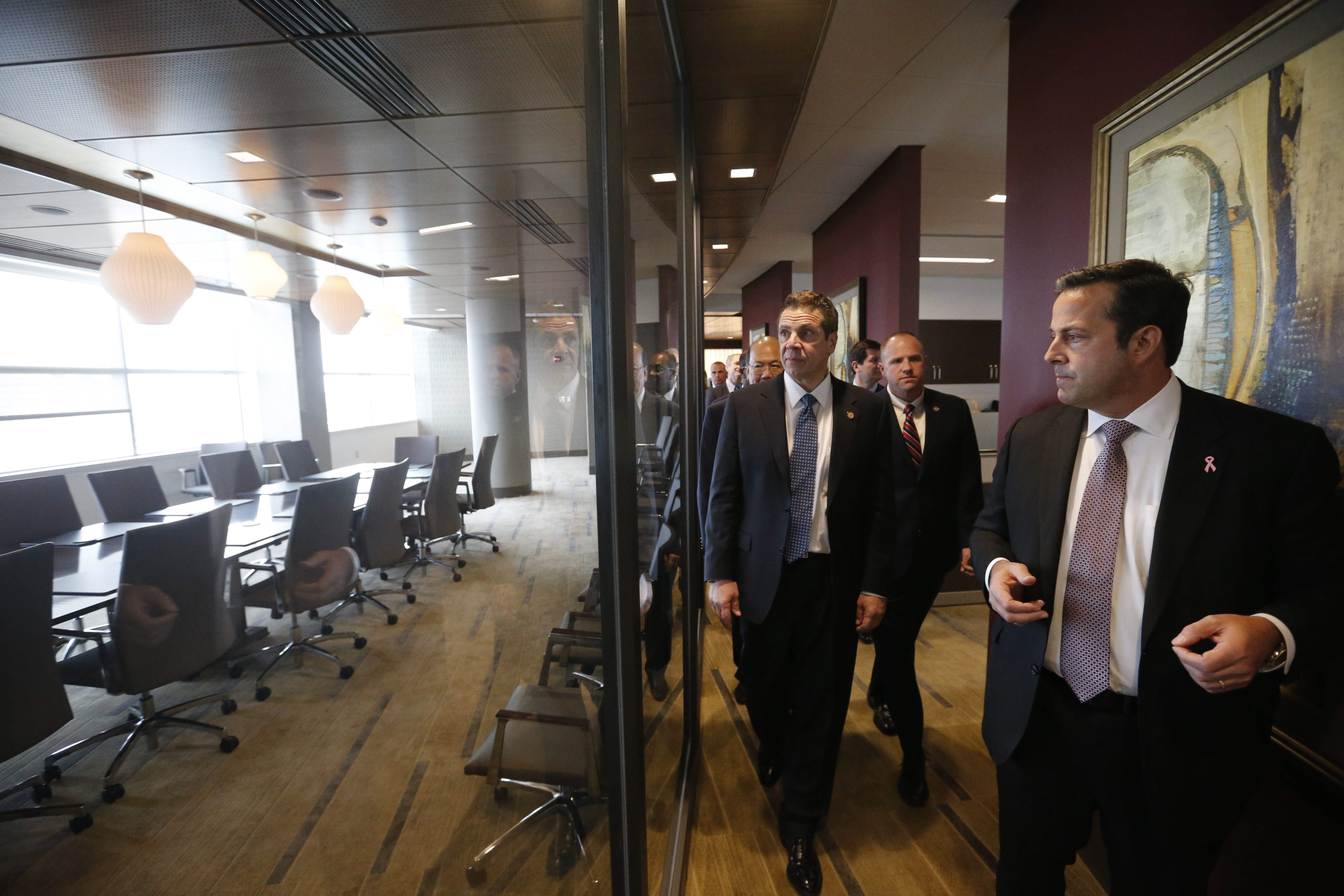 Athenex COO and CFO  Flint D. Besecker, right, gives a tour to Gov. Andrew Cuomo and other dignitaries inside the new Athenex facility at Conventus in February 2016.  (Derek Gee/News file photo)