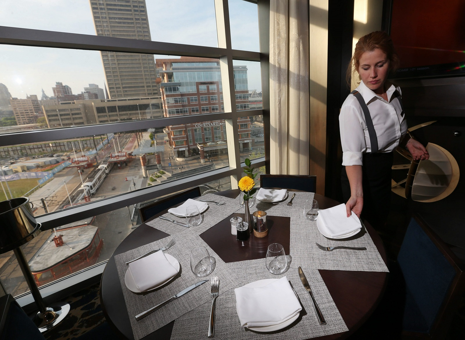 Panorama on Seven bartender-server Leacel Hillenbrand sets a table for dinner. The restaurant in the Marriott overlooks Canalside. (Sharon Cantillon/Buffalo News)