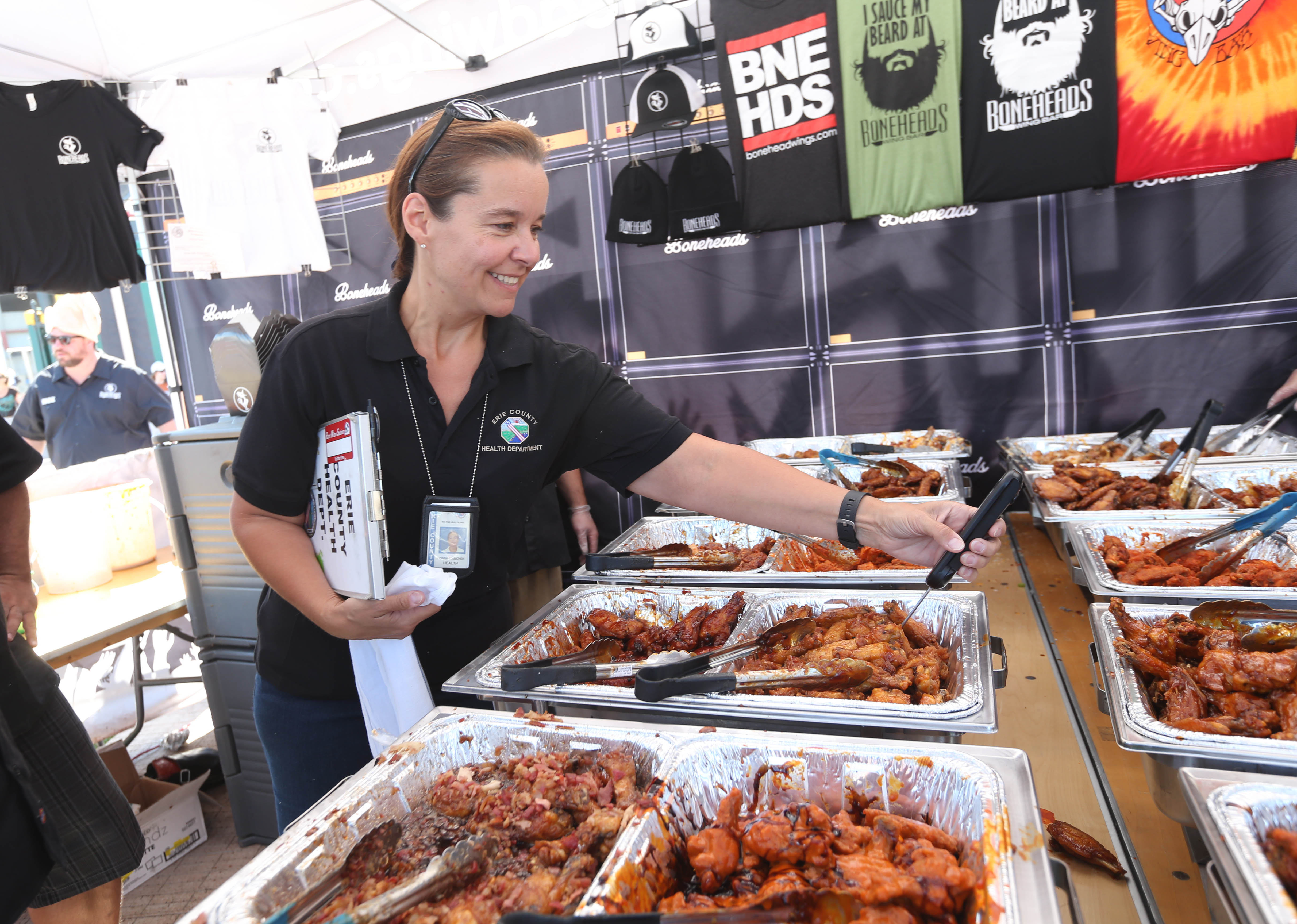 County Health Department Inspector Donna Keicher takes the temperature of wings at a stand operated by Boneheads Wing Bar, from Rhode Island. Temperature is a critical part of food safety. (Sharon Cantillon/Buffalo News)