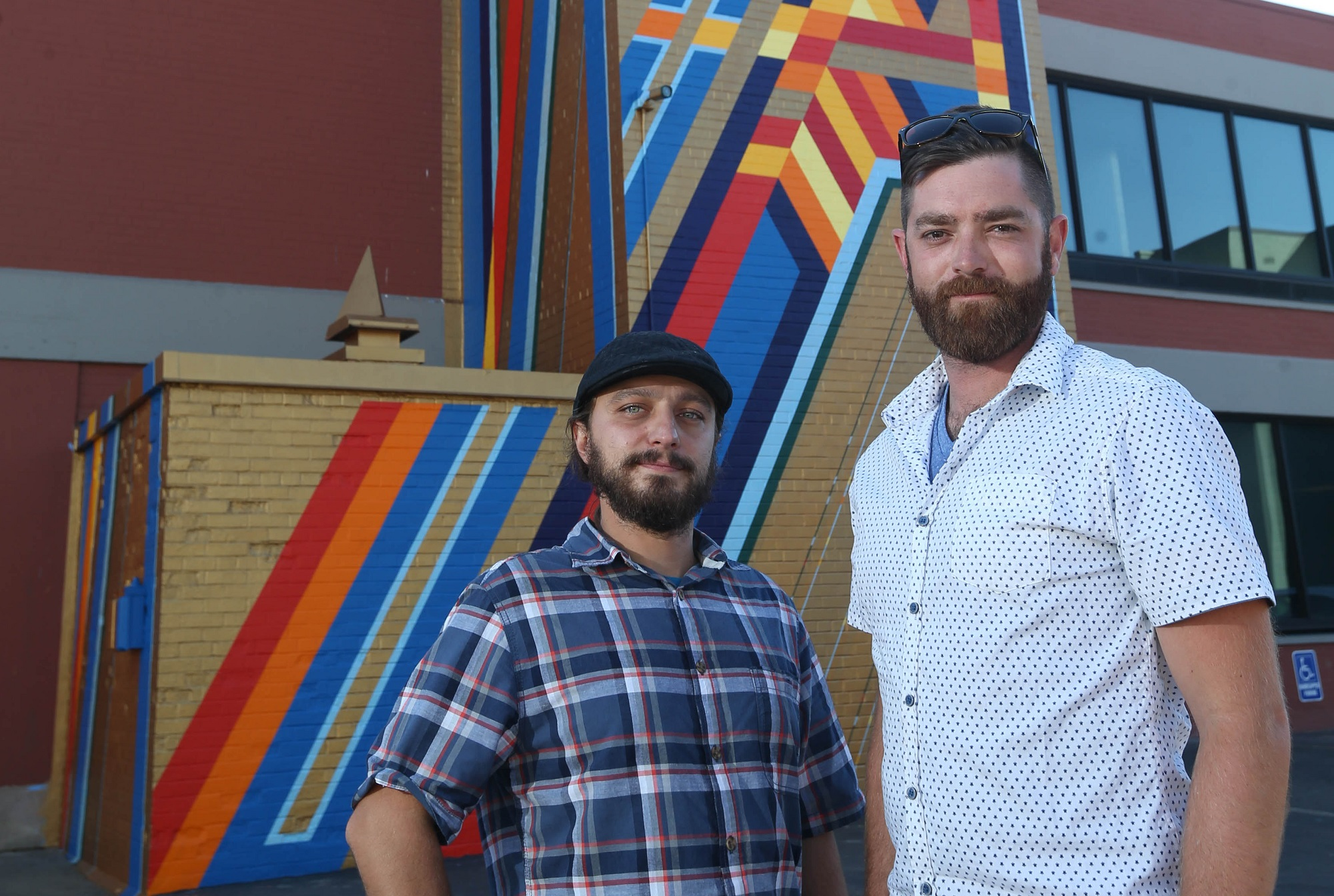 Mural artists Christopher Michael Kameck, left, and Nicholas Conrad Miller - collectively known as Team Razor Wire - just finished their geometric style Tower of Power at 45 Jewett Pkwy. (Sharon Cantillon/Buffalo News)