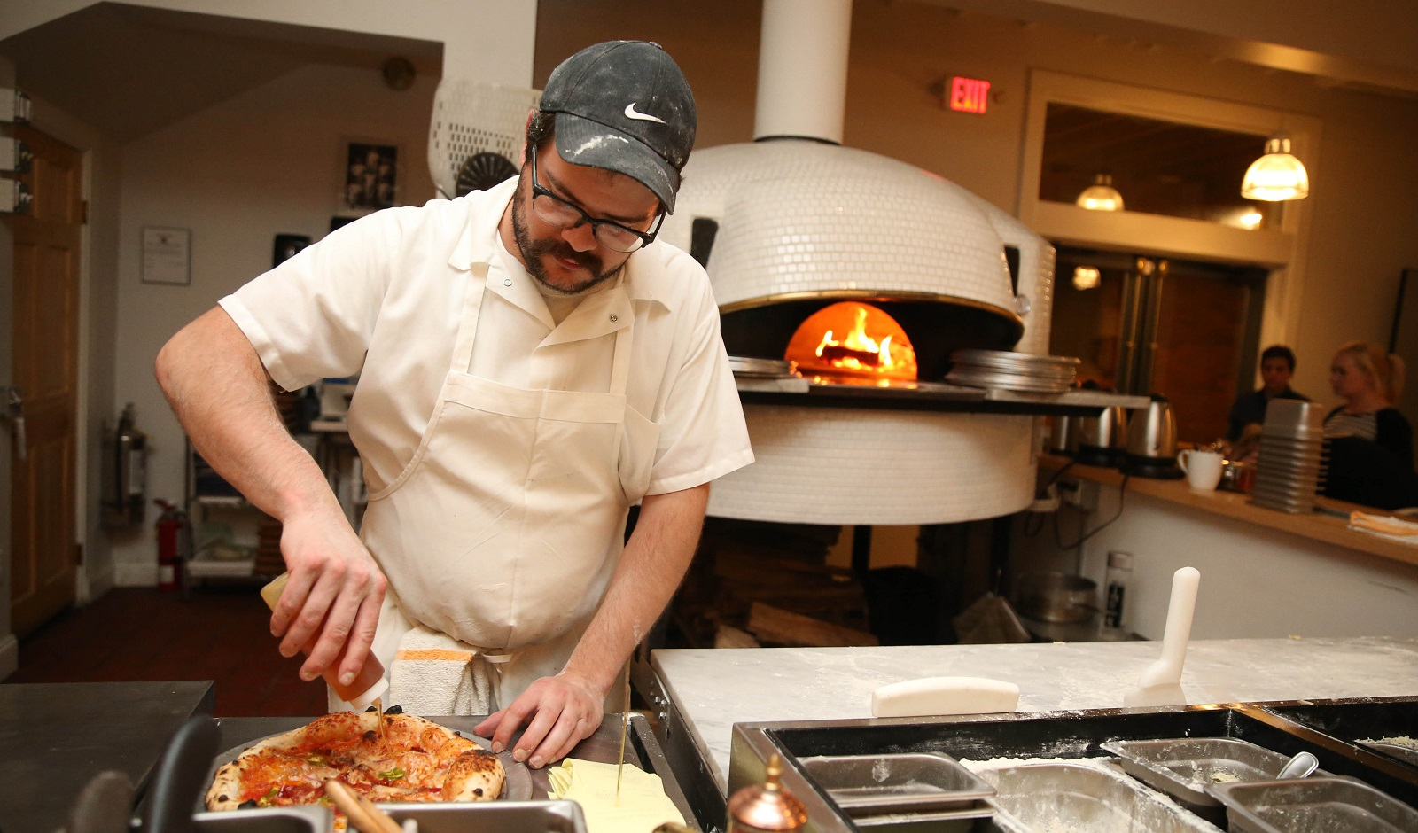 The Grange's Mike Thurkins puts the finishing touches on a pizza.  (Sharon Cantillon/Buffalo News)