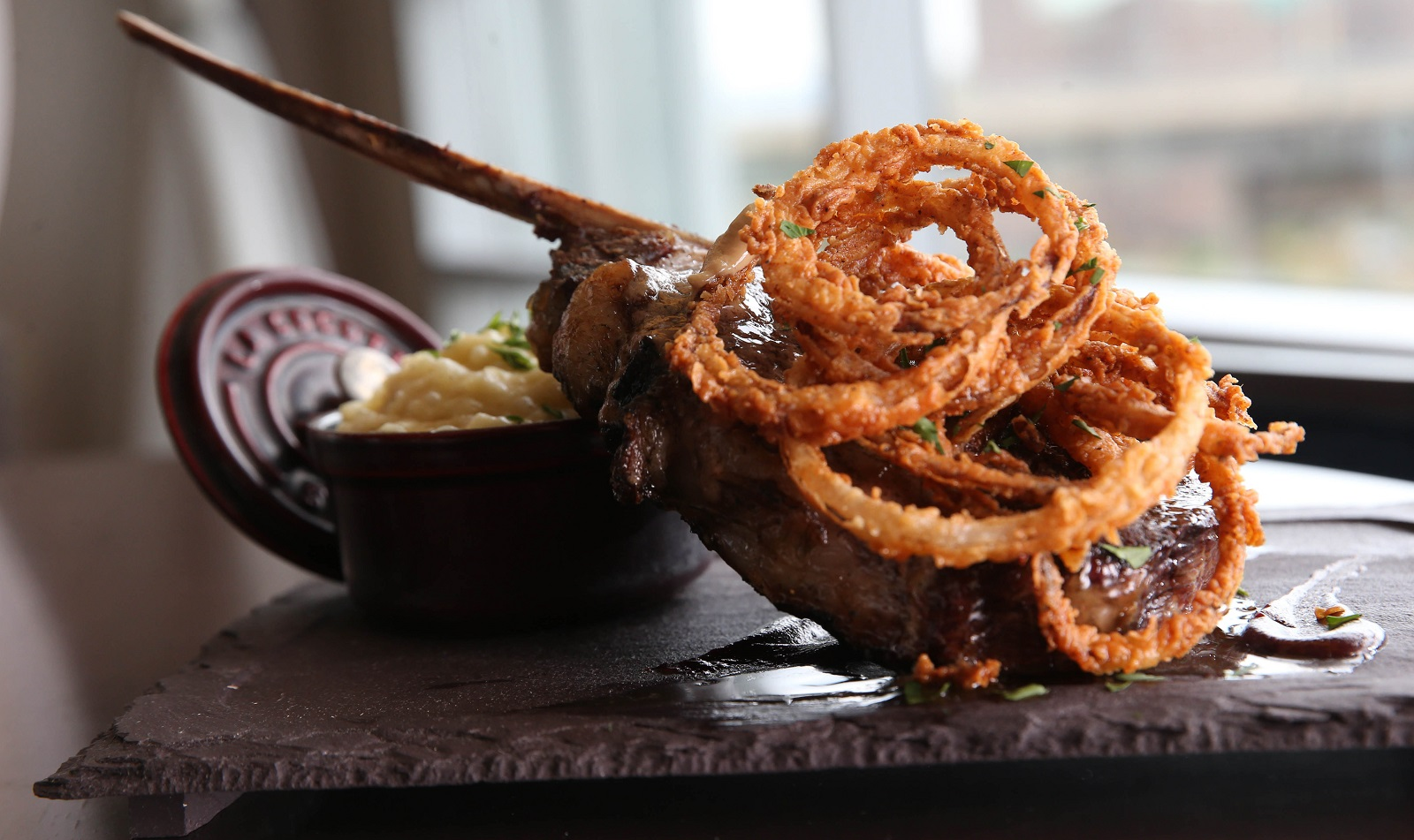 Panorama on Seven's tomahawk steak is a 22-ounce center cut with truffle whipped potato, buttermilk onion straws, a Bordeaux and cherry reduction and foie butter. (Sharon Cantillon/Buffalo News)