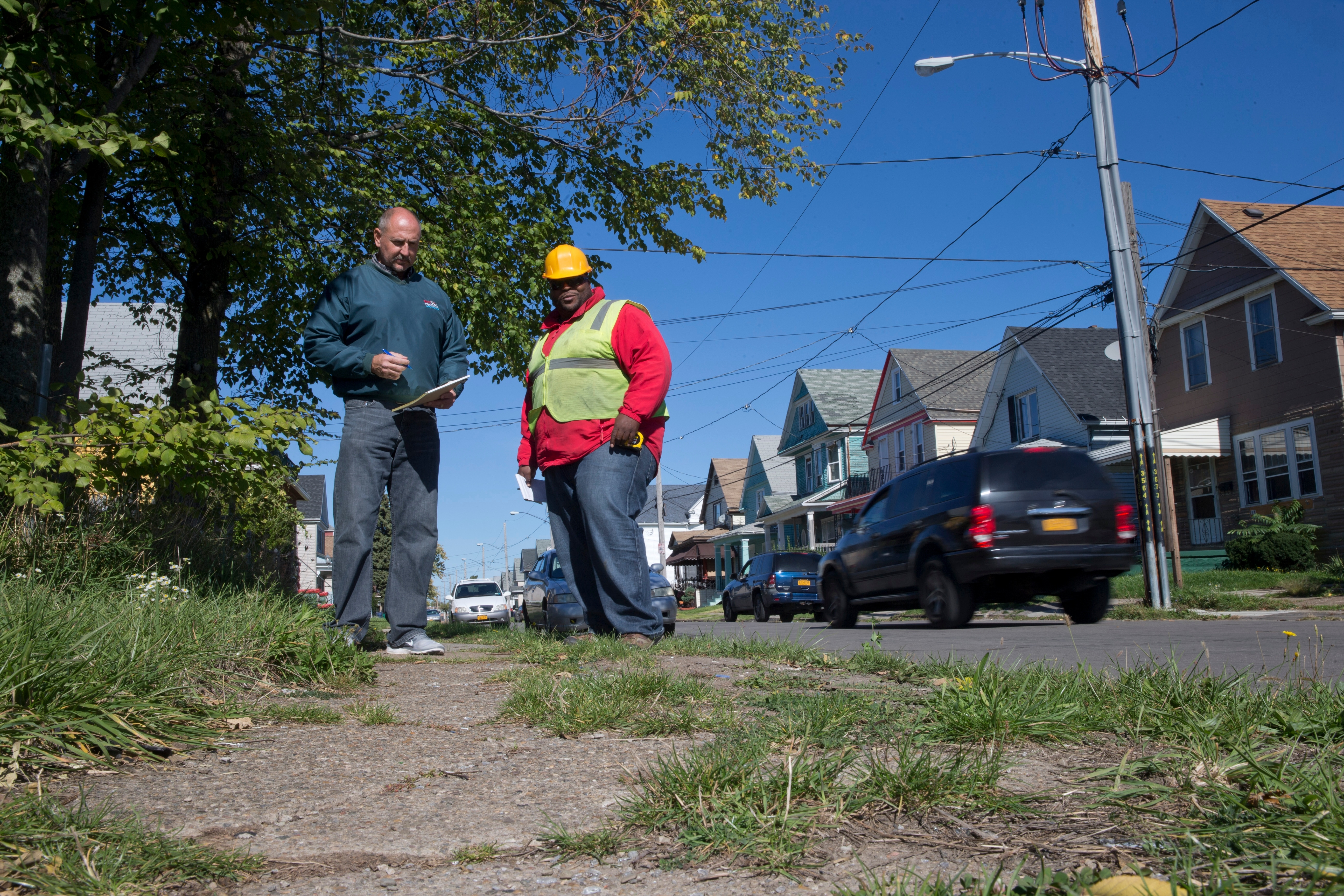 Buffalo Public Works Commissioner Steve Stepniak, left, and Jermaine Skillon, an engineering inspector, walk along Ivy Street in Buffalo to determine which streets and sidewalks need to be repaired. (John Hickey/Buffalo News)