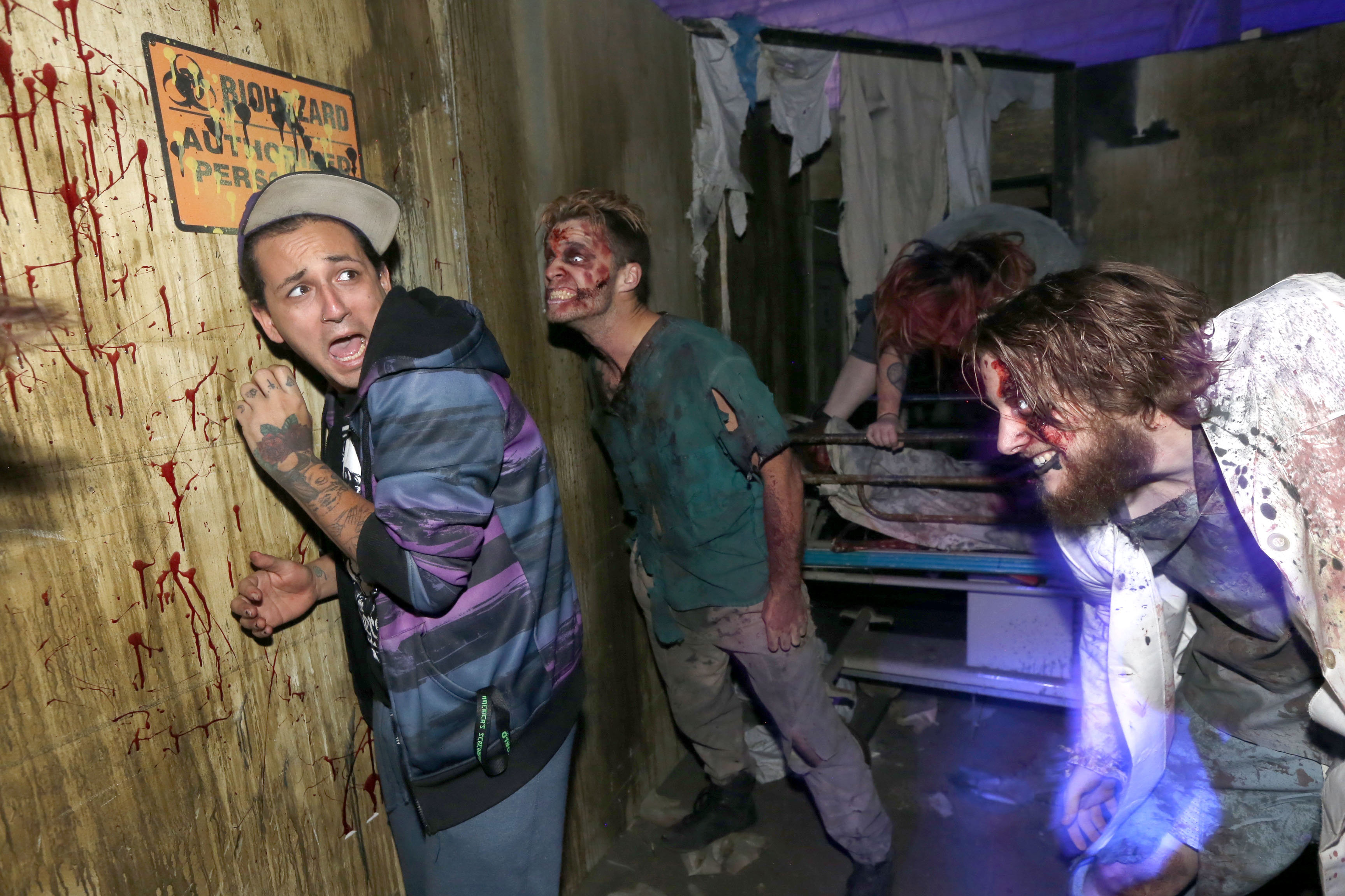Joey Alemany, left, can't find the exit door fast enough when the zombies attack his space in The Asylum at Frightworld on Young Road in Tonawanda.  (Robert Kirkham/Buffalo News)