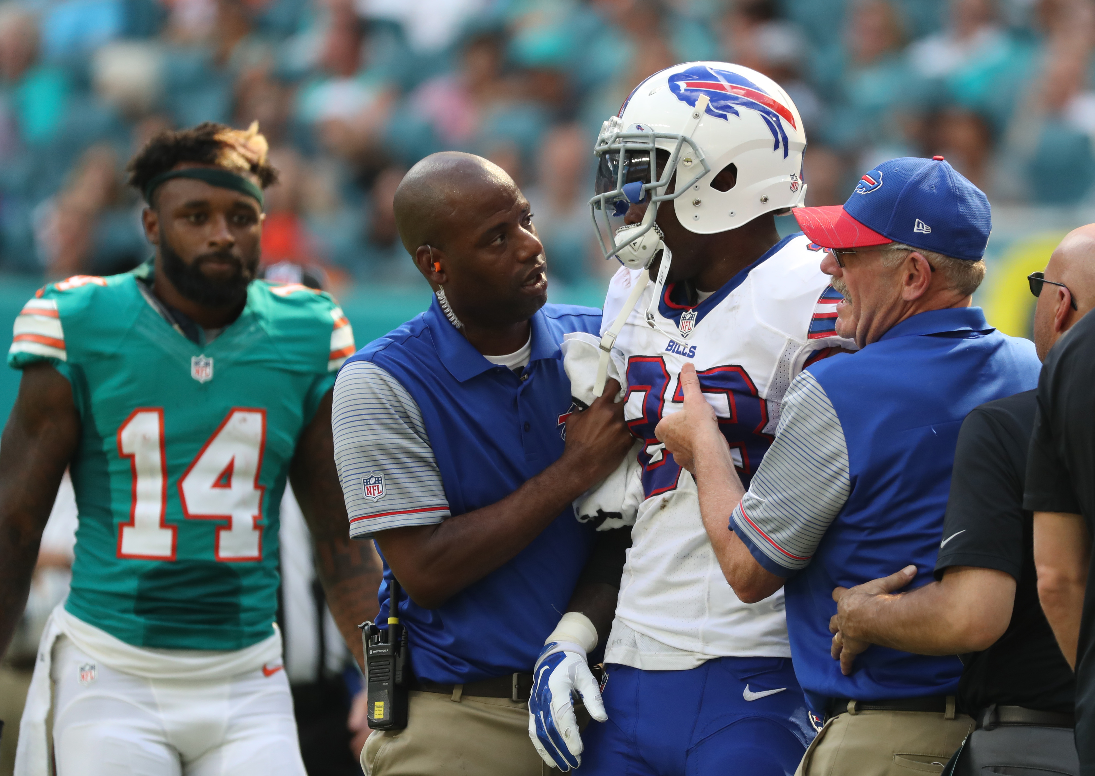 Buffalo Bills strong safety Aaron Williams (23) is helped off the field after being hit by the Dolphins' Jarvis Landry (14, at left).  (James P. McCoy/Buffalo News)
