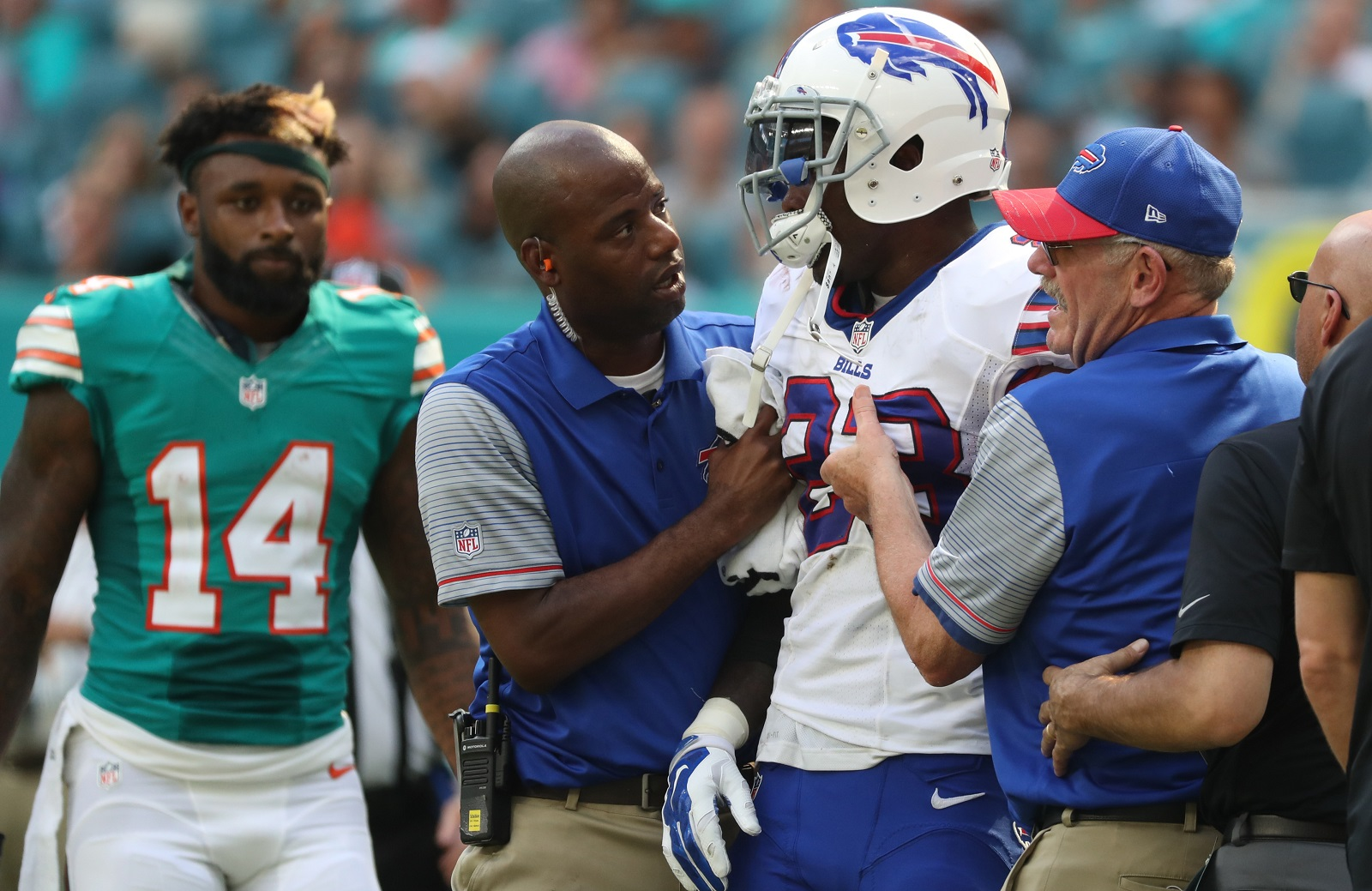 Buffalo Bills strong safety Aaron Williams is helped off the field as Jarvis Landry looks on.  (James P. McCoy/Buffalo News)