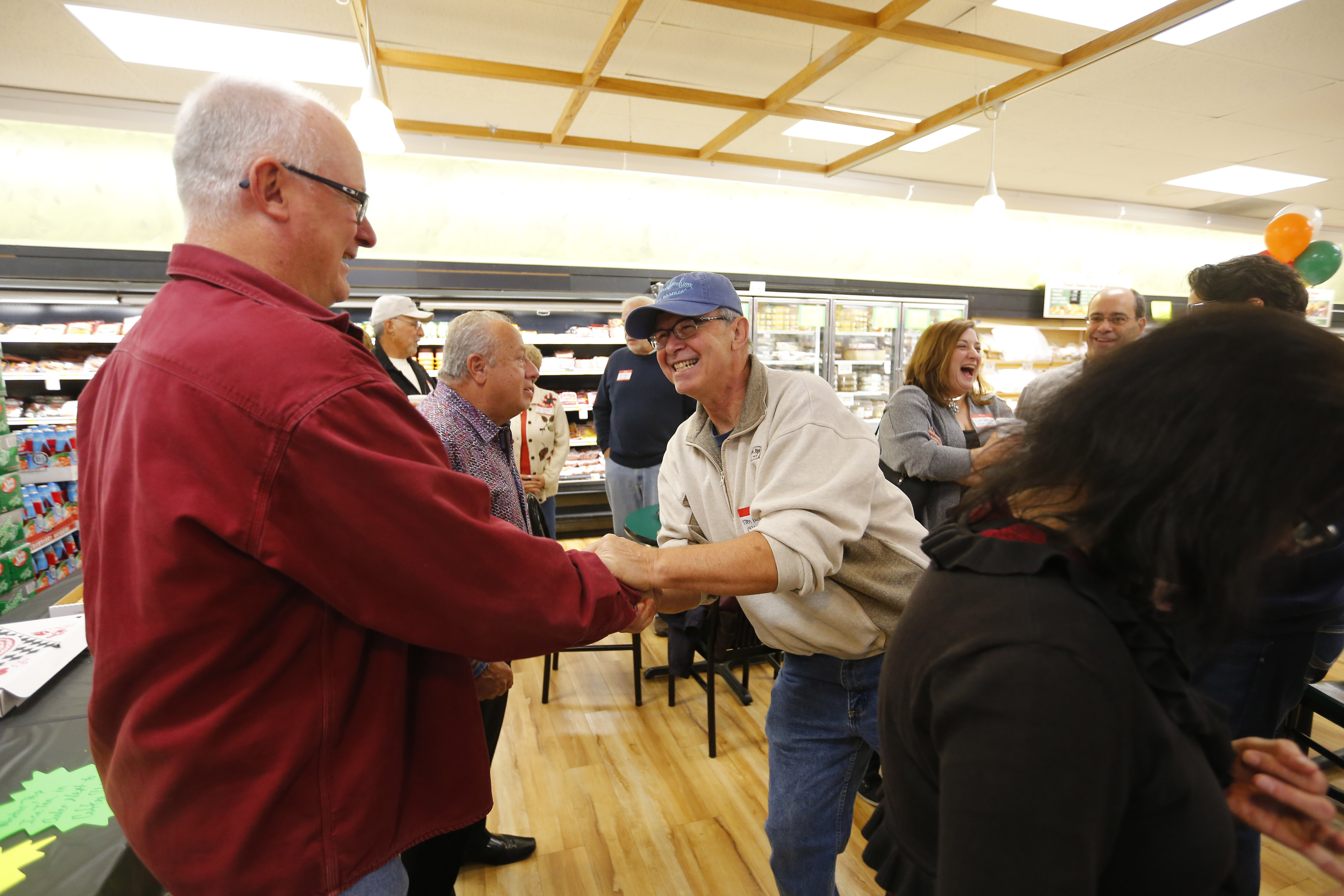 Former Budwey's employees Rick Reimer, left, shakes hands with Tom Ballou, right, during a reunion of former employees at the store in North Tonawanda on Saturday, Oct. 30, 2016. (Mark Mulville/Buffalo News)
