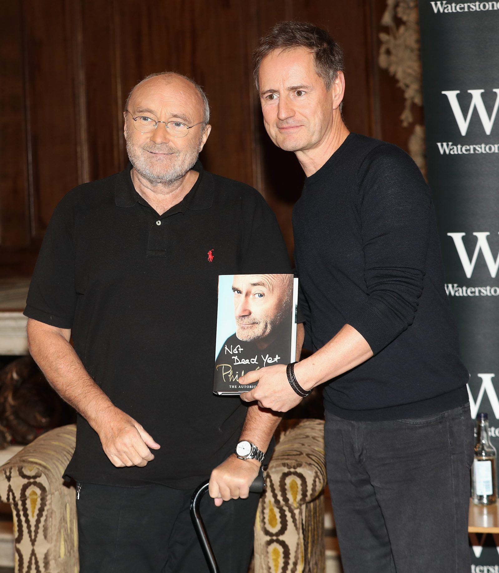 To celebrate the launch of his autobiography Not Dead Yet, Phil Collins poses with Magic FMs Richard ahead of a talk at in London.  (Photo by Chris Jackson/Getty Images)