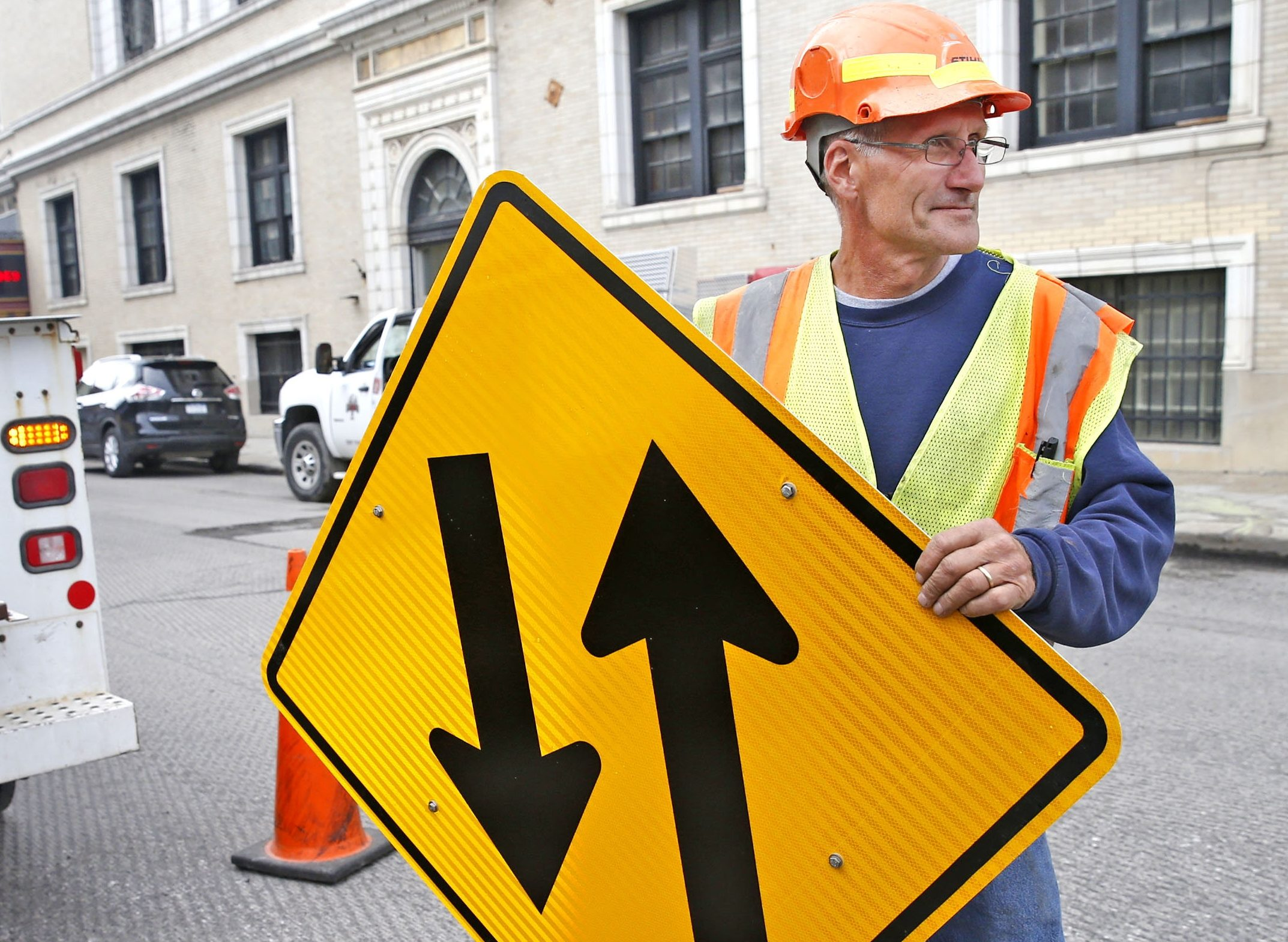 Ken Thomas, a construction worker for Concrete Applied Technologies Corp. of Alden, prepares for installation of a new two-way sign on Pearl Street in downtown Buffalo. On Tuesday, crews will start final paving of one-mile stretch from West Tupper to Lower Terrace.