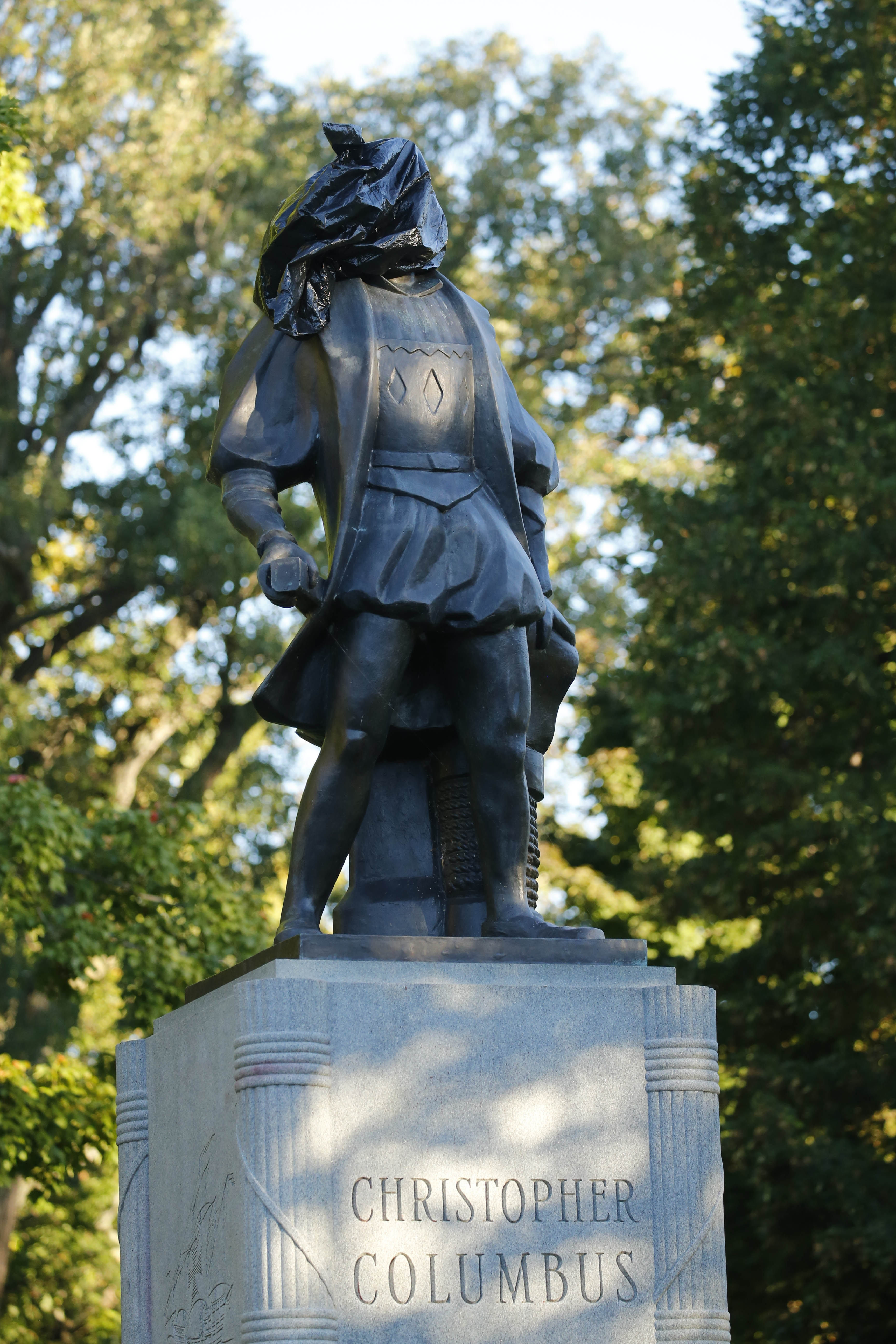 """A plastic bag was placed on the statue of Christopher Columbus in Prospect Park Monday in an anonymous protest of Columbus Day. A message in chalk on the walkway leading to the statue read: """"Columbus was a slaver & a rapist."""""""