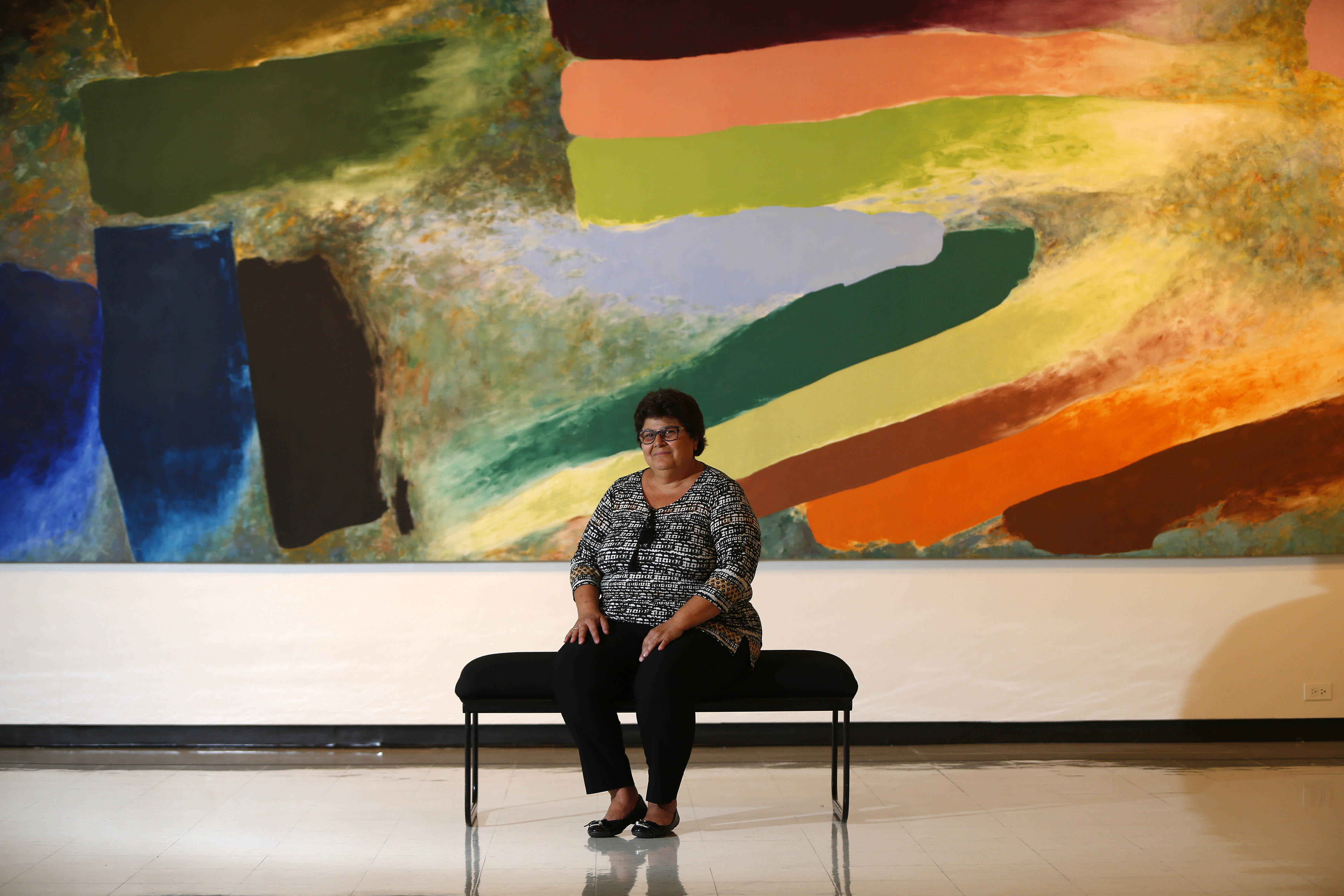 "Anne Marie DiMino-Hepfer will receive the Castellani Art Museum's first Legacy Award at the CAM's 14th annual gala  on Saturday at the Niagara Falls Conference and Event Center.  She is shown seated Thursday, October 6, 2016 in front of a painting entitled ""Grand Mesa,"" by American artist Friedel Dzubas at the art museum.  It's a 1977 acrylic on canvas that was donated by Armand and Eleanor Castellani. (Mark Mulville/The Buffalo News)"