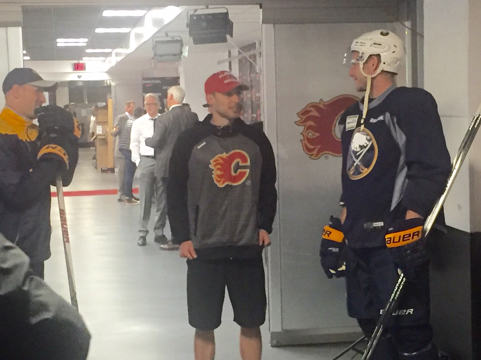 Former Sabres goalie Chad Johnson chats with Cody Franson and Buffalo goaltending coach Andrew Allen Tuesday in the Saddledome (Mike Harrington/Buffalo News).