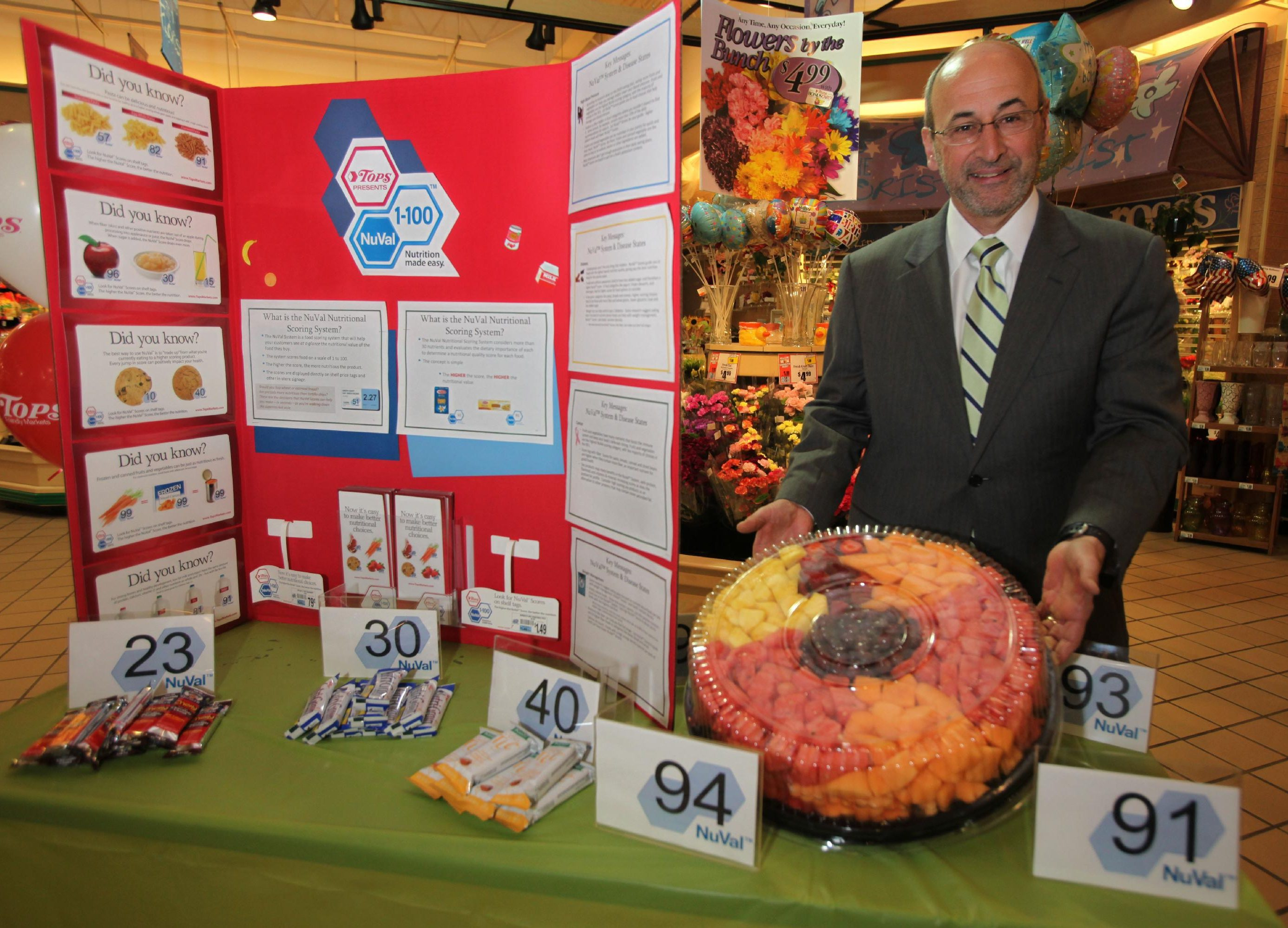 Tops Market Chairman and CEO Frank Curci holds a fruit tray at a display designed to highlight the new NuVal Nutritional Scoring System placed in all Tops locations.