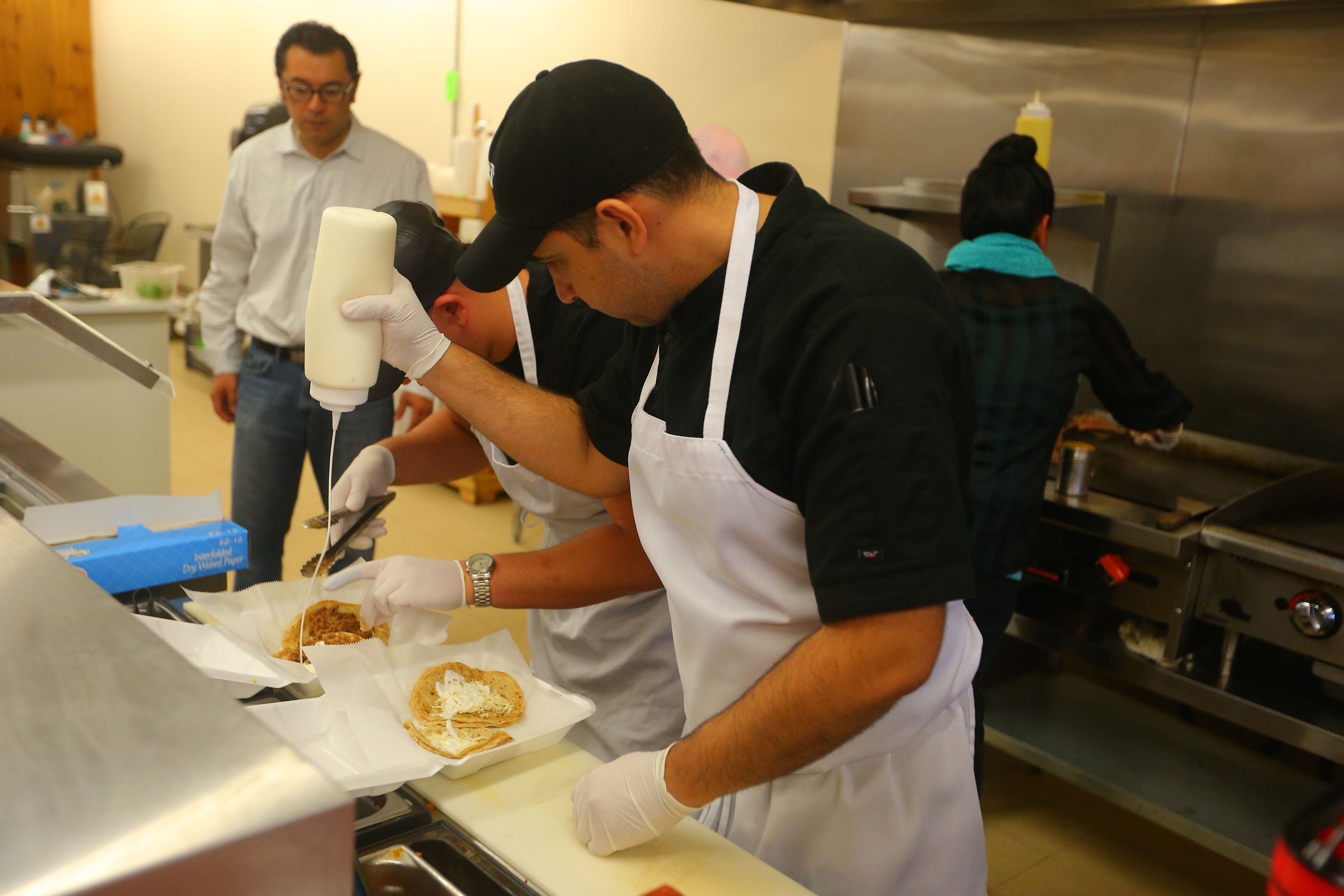 Sergio Mucino, left, looks on as workers put together a take out order at La Divina Mexican Store on Friday Oct. 21, 2016, La Divina Mexican Store reopened after briefly closing following a raid by federal agents and the arrest of Mucino and several employees, in Kenmore, N.Y., earlier this week. (John Hickey/Buffalo News)