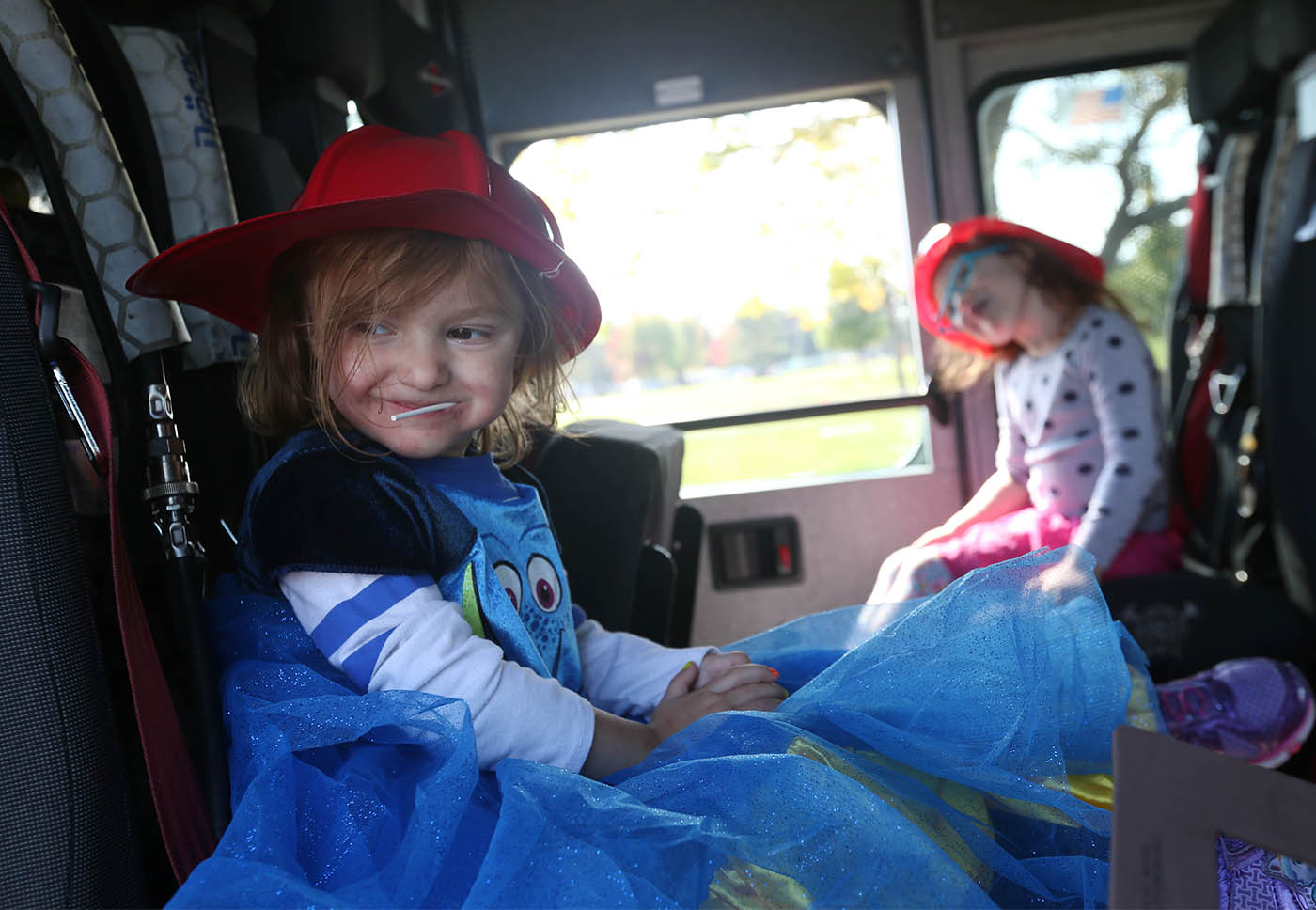 Elmlawn Memorial Park in the Town of Tonawanda, holds its second annual Family Fall Fest, Sunday, Oct. 16, 2016. The Town of Brighton Volunteer Fire Company has a truck onsite to let kids see the inside and to receive toy fire helmets. Sisters Victoria Goodwin, 3, of Buffalo, left, and Ellie, 4, sit in the seats in the cab of the truck. (Sharon Cantillon/Buffalo News)