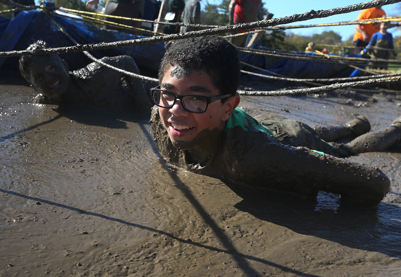 Bernard Carroll,12, of Troop 400 Hamburg crawls through the mud pit as he and other Boy Scouts and others participated in a Scout Strong 5k mud run and obstacle course at a big scout camporee at Beaver Island State Park, in Grand Island, N.Y. on Saturday Oct. 15, 2016. (John Hickey/Buffalo News)